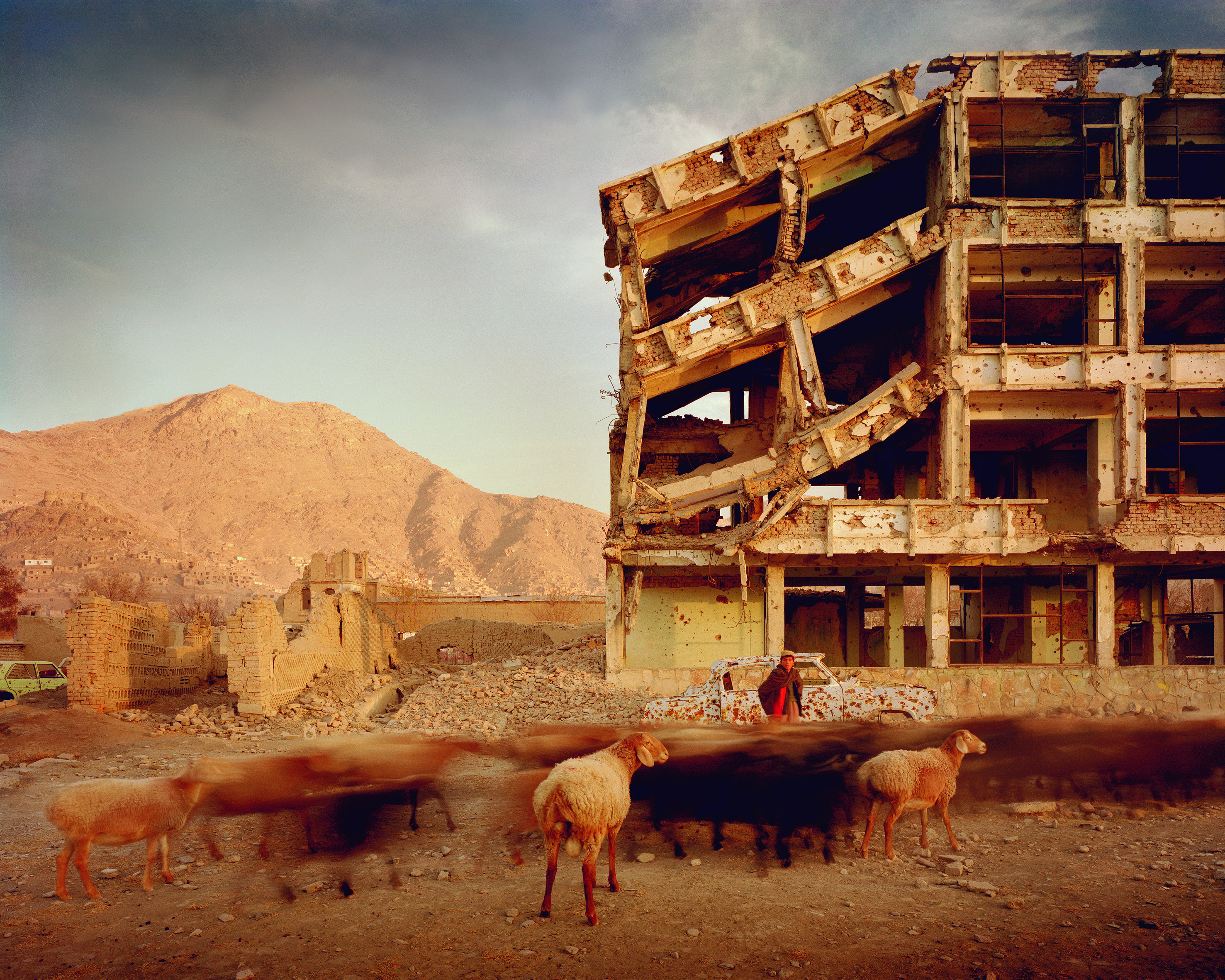 Simon Norfolk Bullet-scarred apartment building and shops in the Karte Char district of Kabul. This area saw fighting between Hikmetyar and Rabbani and then between Rabbani and the Hazaras  2003 © Simon Norfolk