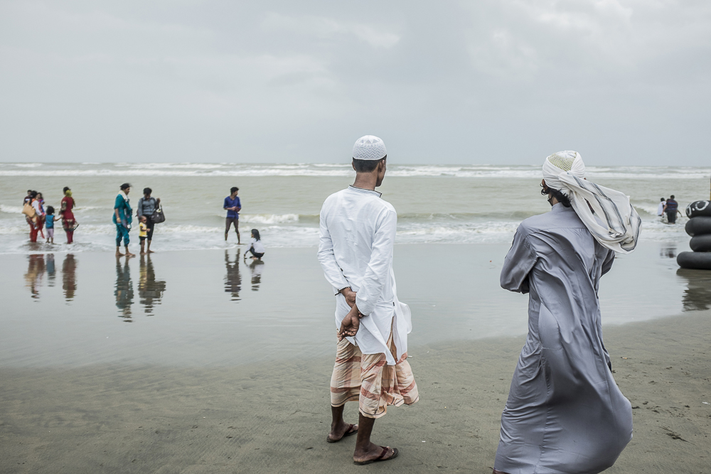 Two young men, watching the sea on Cox's Bazar's beach, Banglade