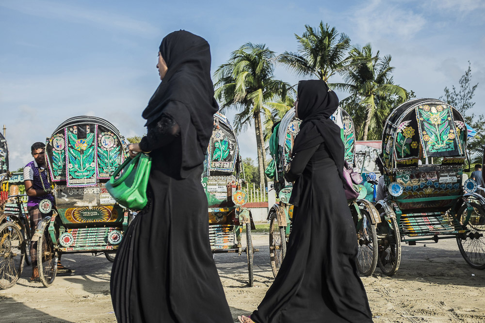 Two young muslim women walk out from the beach of Cox's Bazar, B