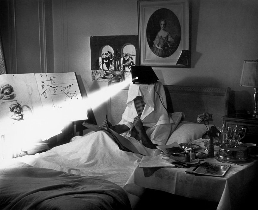 "DALI in bed, projecting pieces of dirty paper ""to stimulate his inspiration""."