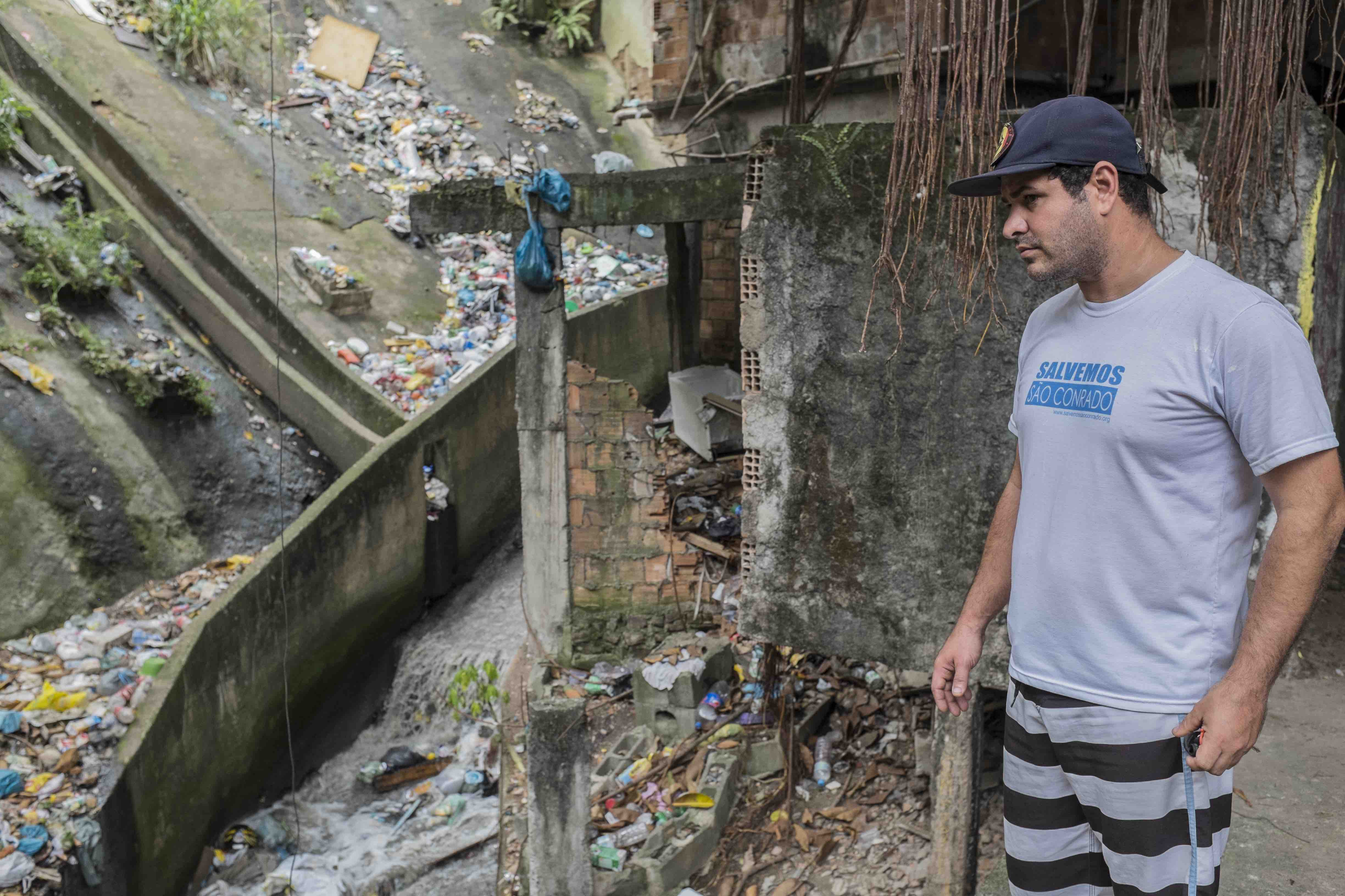 Marcello Farias in front of a polluted drain in Lajão, Rocinha.