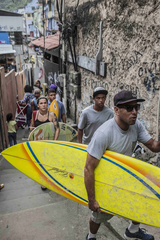 Young surfers, led by surf school founder Bocão, climb Rocinha's narrow streets.