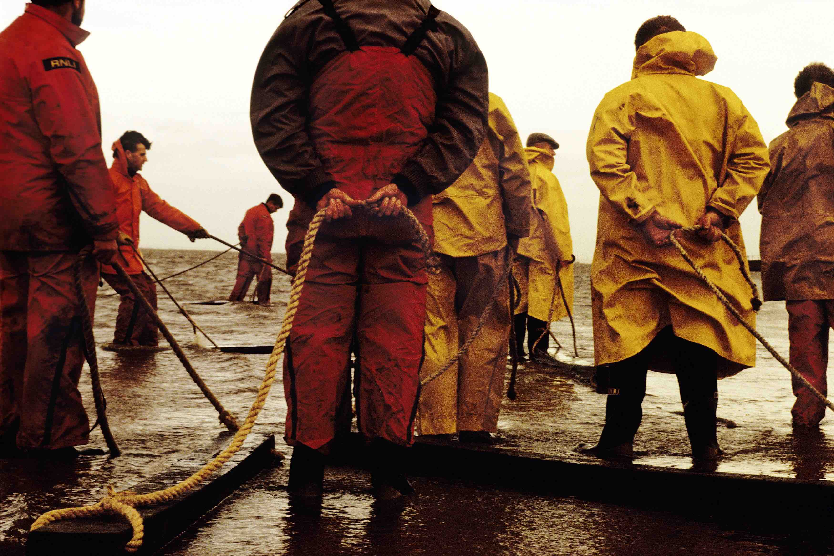 Hoylake lifeboat crew in 1991. Backs of the crew on the shore with ropes.
