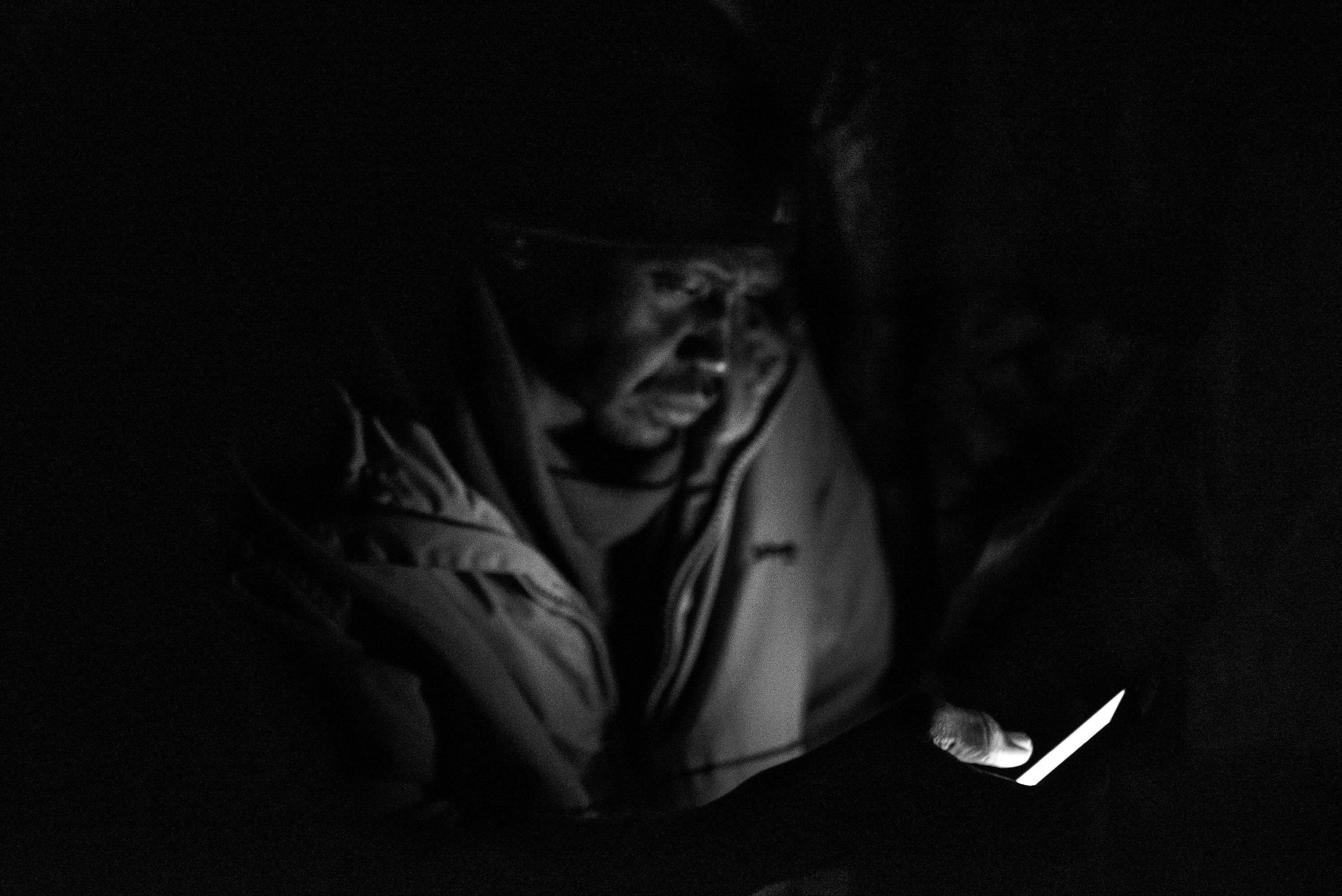 In the evening Ahmad stays in his shelter, using his phone to speak with relatives and friends.