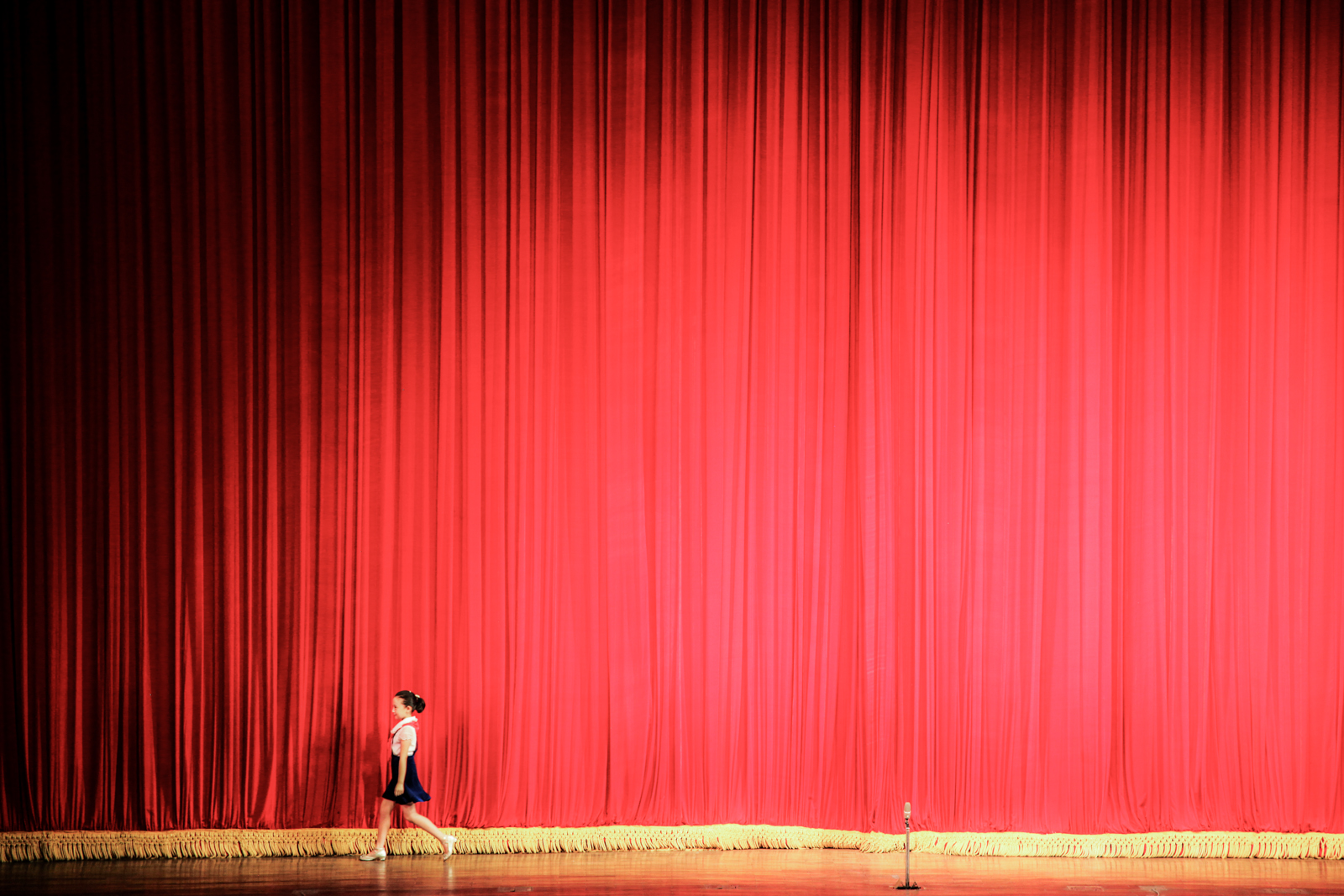 A young singer walking past the red curtain of a theatre inside the Children's Palace, Pyongyang.