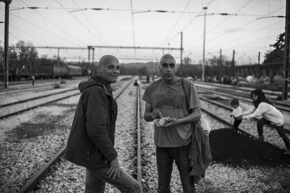 Karim (left) and Hassan (right) from Algeria, standing in the centre of the tracks outside Idomeni Station. An outbreak of lice in the camp means many of the residents have shaved their heads.