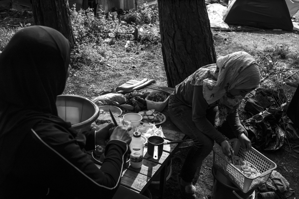 Amira (left) and Shayma (right) peeling potatoes in their campsite above the road leading to the Macedonian border. They have been living in the camp for two months after fleeing Raqqa in Syria.