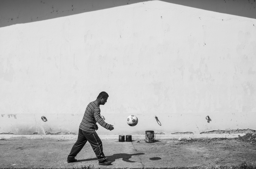 A Yazidi boy plays football against a wall that houses refugee families.