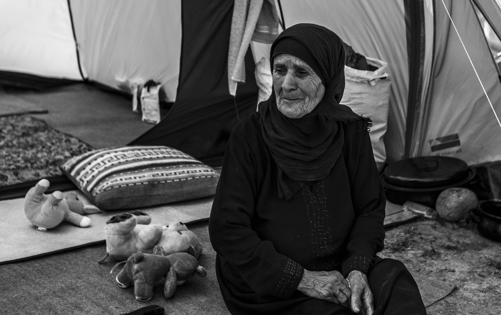 Aseel from Homs, Syria sits in the entrance to her tent in Idomeni.