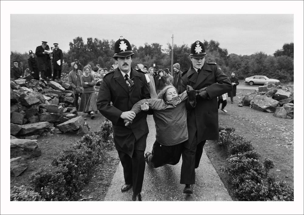 A protestor from the Women's Peace Camp is arrested for obstructing building work outside the Main gate at RAF/USAF Greenham Common, Berkshire (1982)