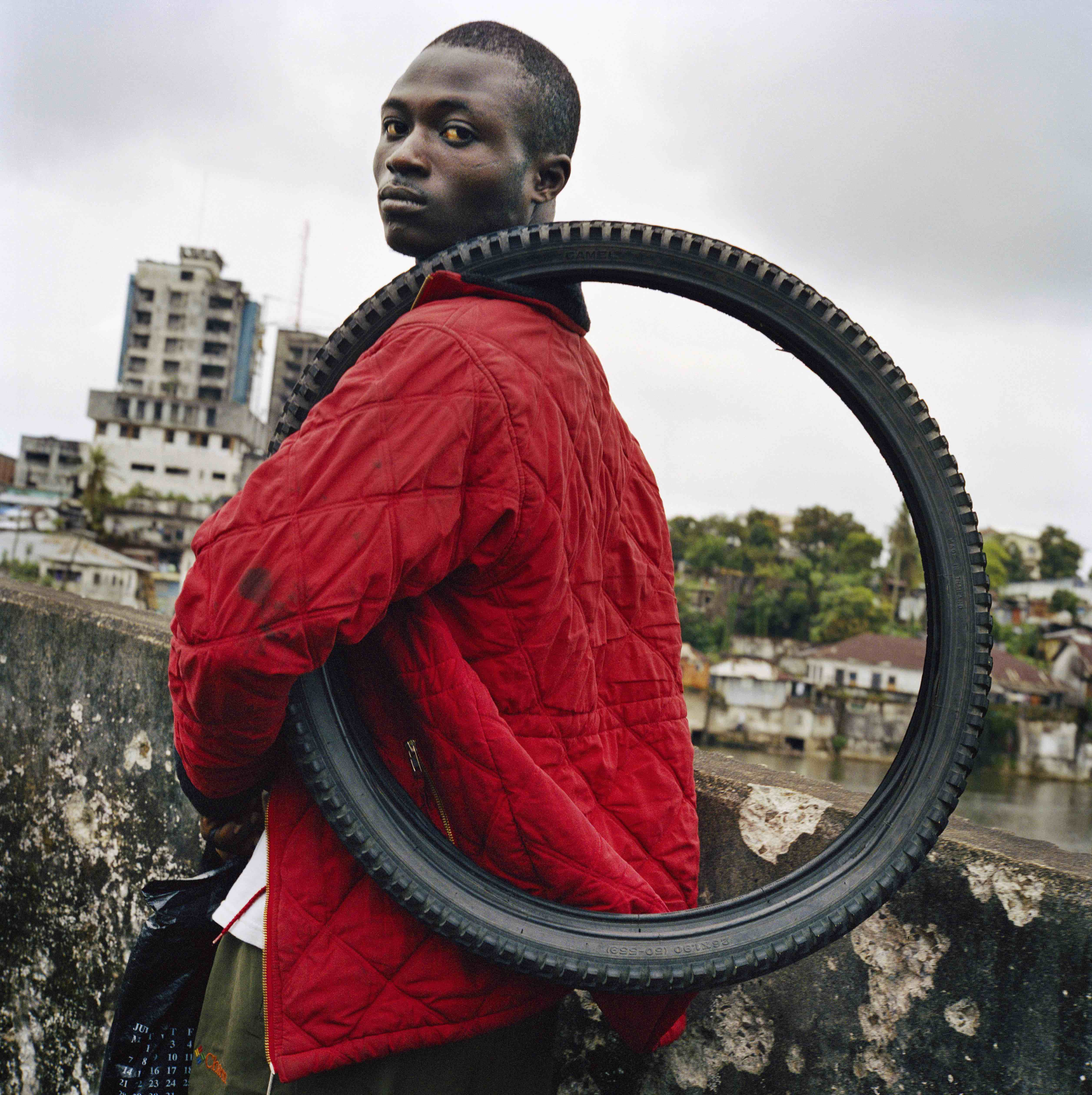 LIBERIA. 2003. Young man on the Gabriel Tucker bridge in central Monrovia carries a tyre which he is trying to sell. Liberia is one of the world's largest rubber producers and home to the Firestone Rubber Plantation. © Tim Hetherington / Magnum Photos