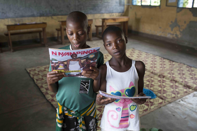 Two girls in the 12+ classroom with copies of Ni Nyampinga