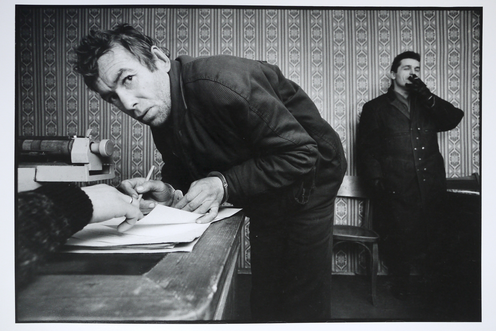 A petty thief signing his confession at the local police station. The arresting officer stands in the background, December 1992.