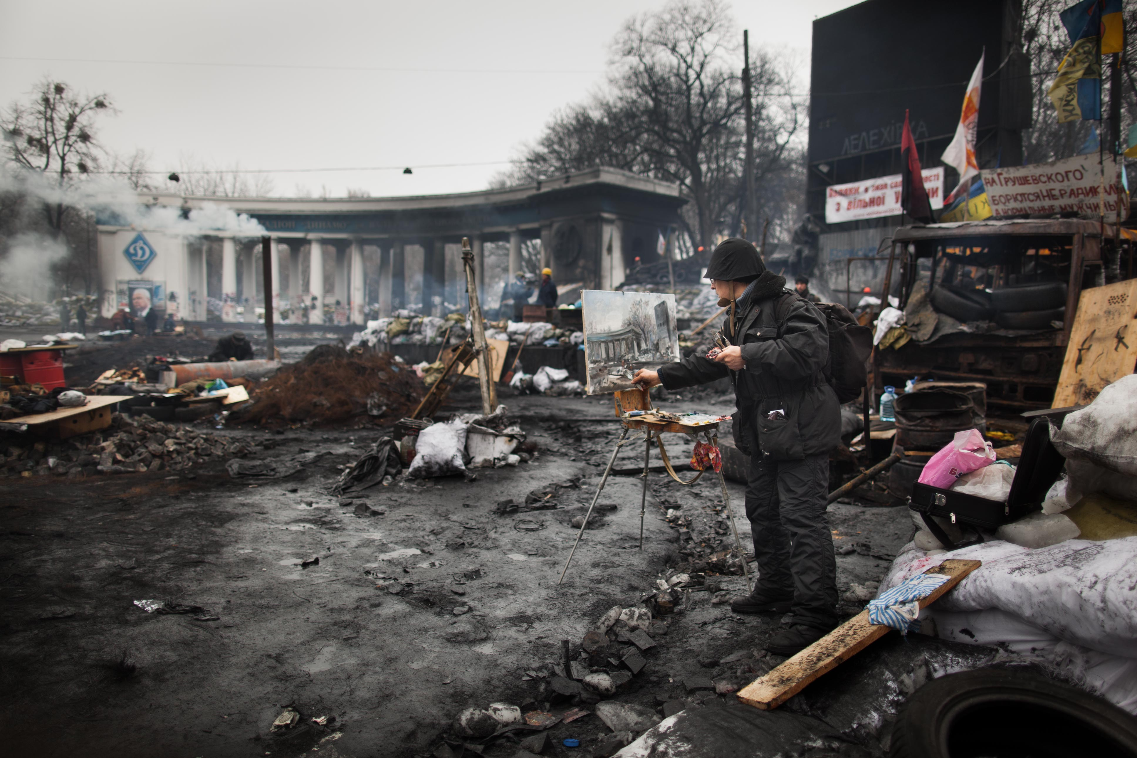 An artist paints during Ukraine's Maidan protests, February 2014.