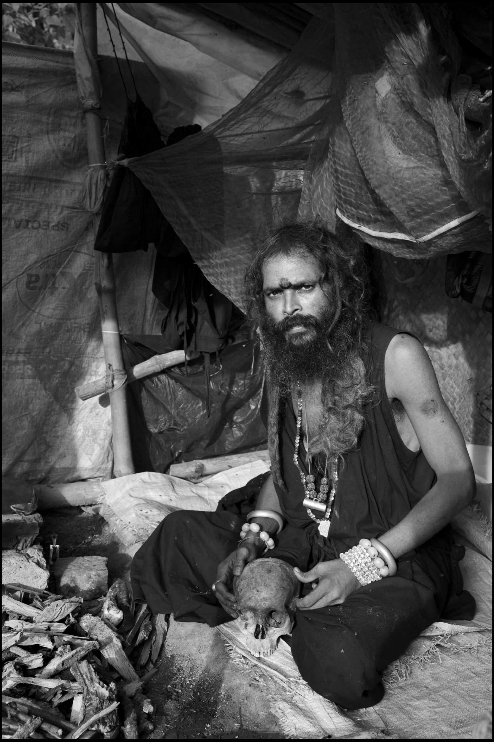 In the grounds of the Bamakhepa burning ghat, a Tantric sannyasi uses the skull of his dead guru 'to enhance his spiritual powers' during meditation; Tarapith, India.