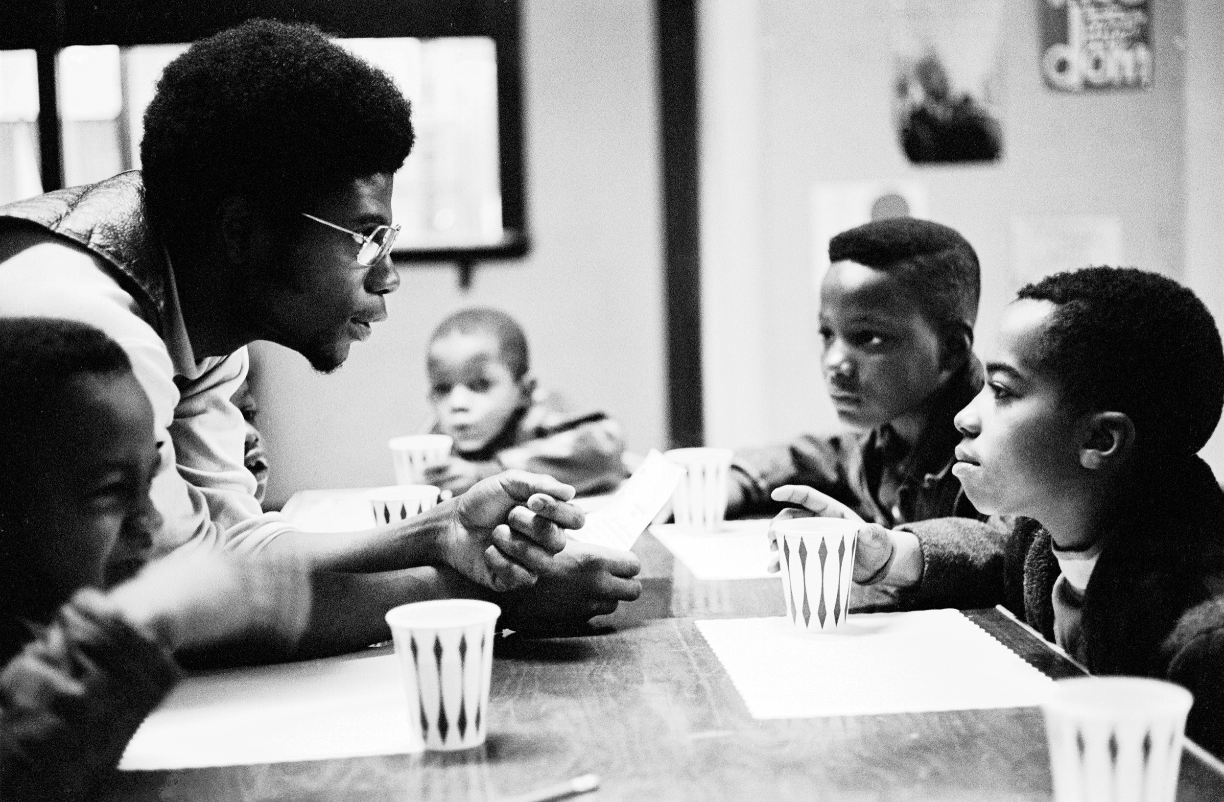 "Panther Jerry ""Odinka"" Dunigan talks to kids while they eat breakfast on Chicago's South Side, November 1970"