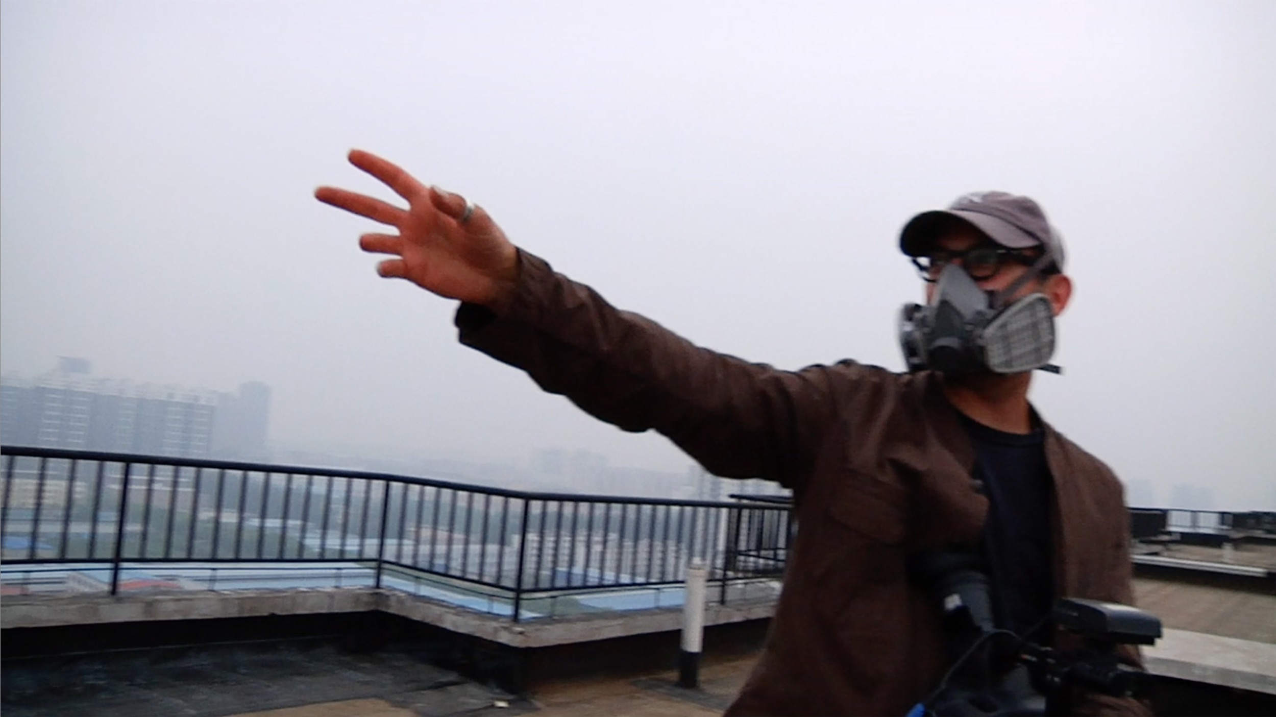 Josh Fox gestures to the oppressive smog from a rooftop in Beijing.