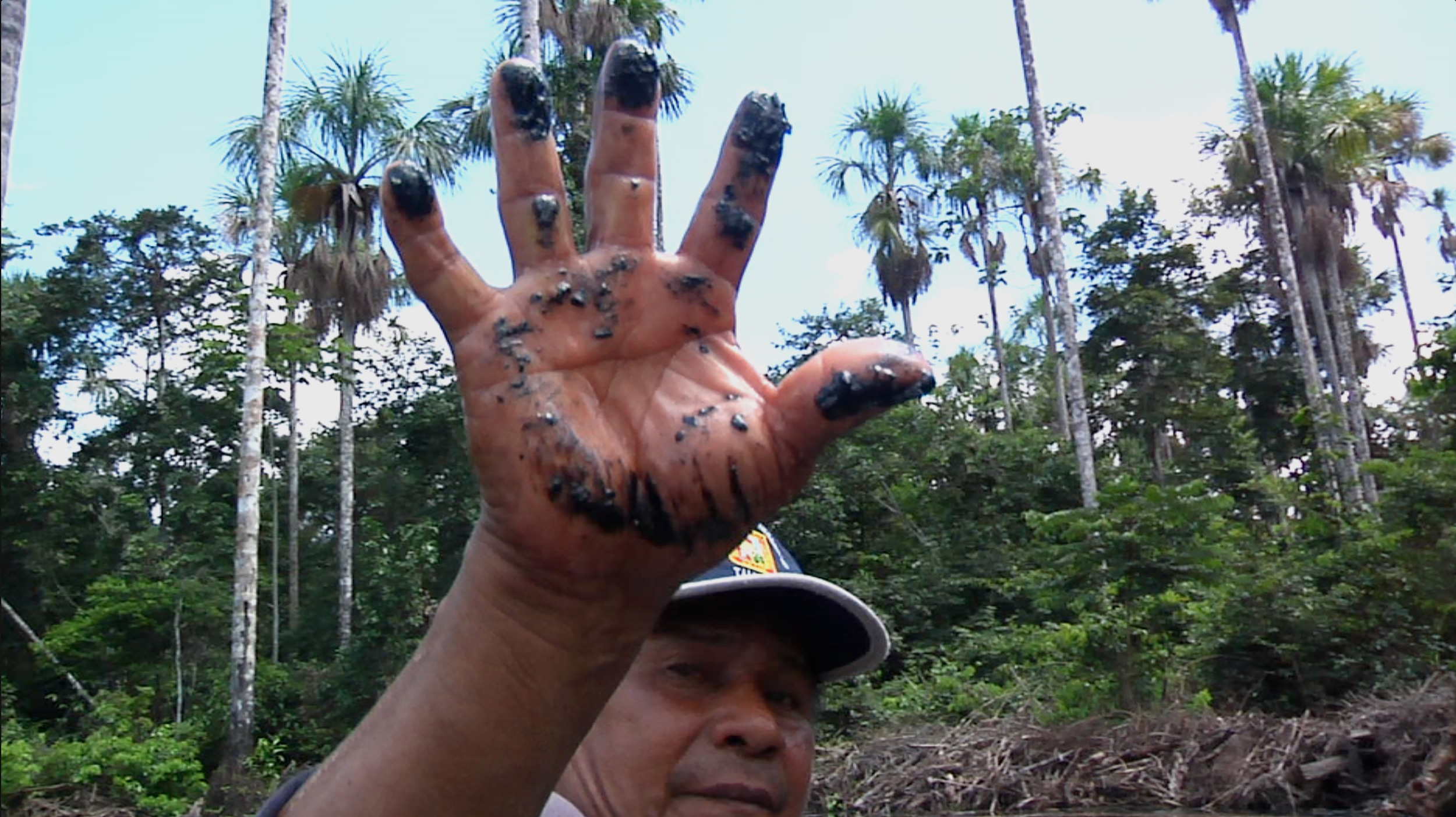 A local resident shows the oil residue left behind along an Amazon tributary from a pipeline spill that has supposedly been remediated.