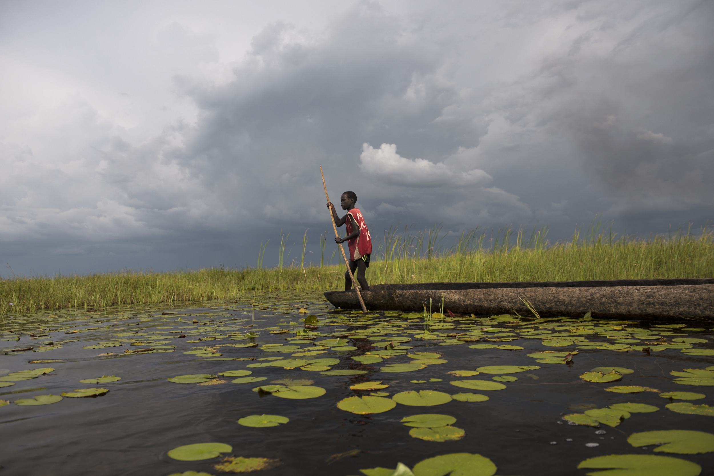 Nine-year-old Chuol fishes for tilapia in a  vast swamp in South Sudan after fighters swept into  his village, September 2015.