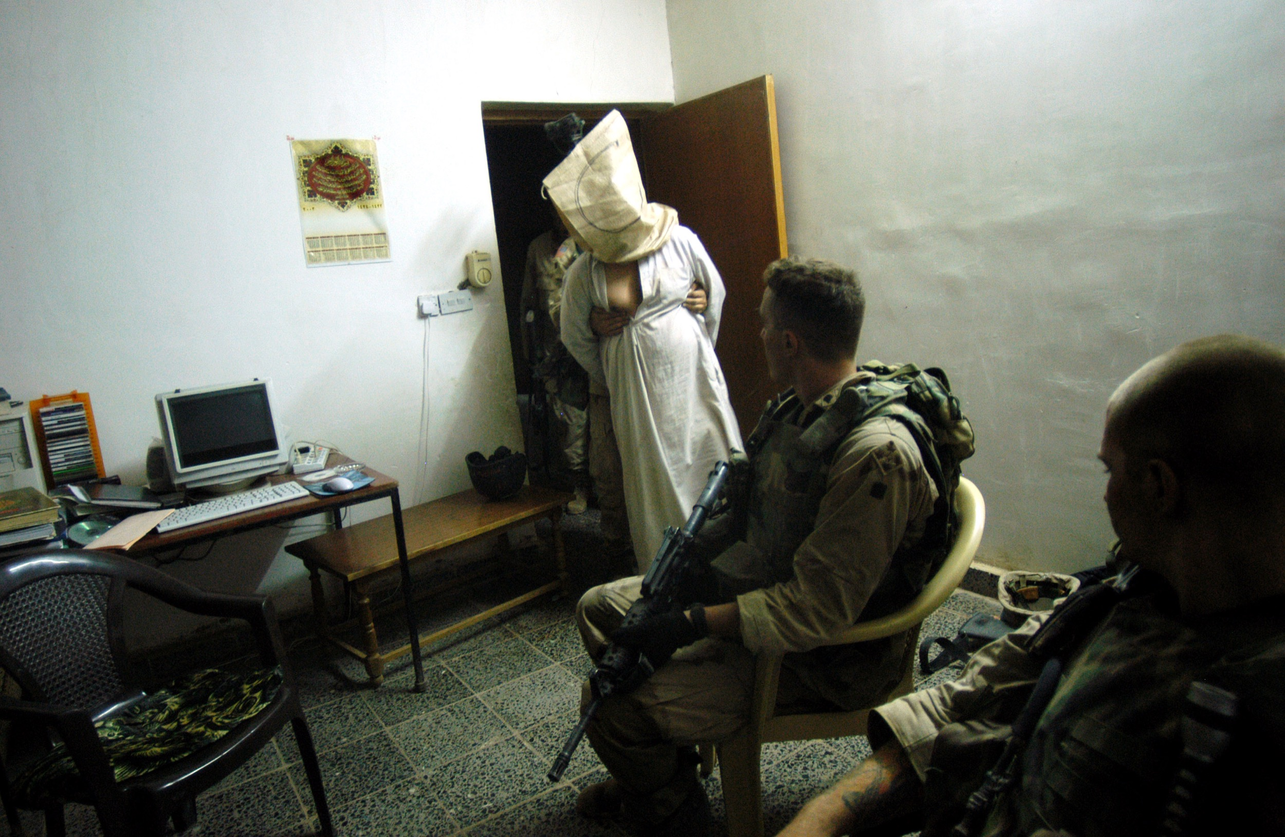 US soldiers stand over detained Iraqis, believed to be supporters of former Iraqi leader Saddam Hussein, 30km north of Baghdad, June 2003.