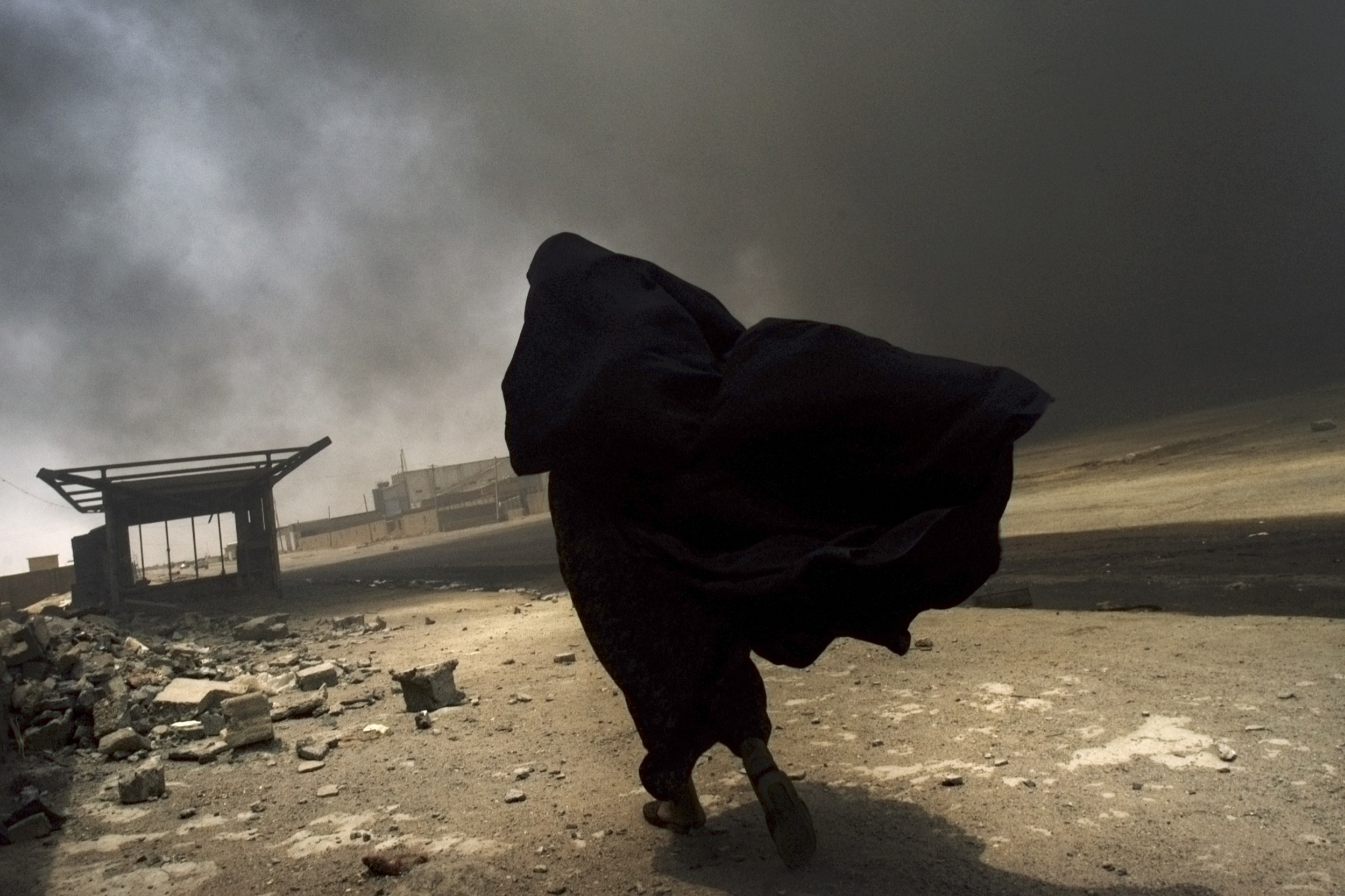 An Iraqi woman searches for her husband at the site of a liquid-gas factory fire, allegedly set by looters in Basra, May 2003.