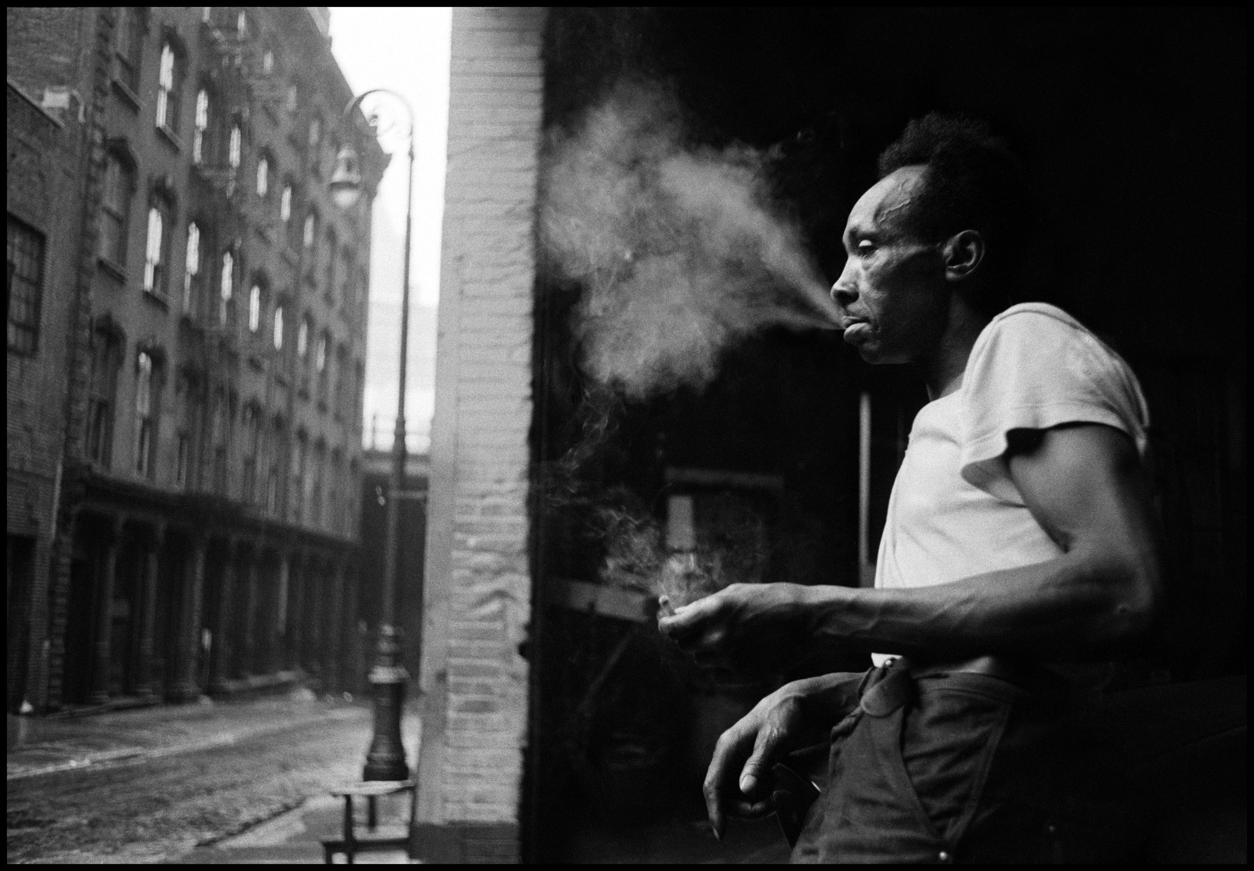 USA. New York City. 1955. Man smoking in the streets under the Brooklyn Bridge. Photo by Erich Hartmann.