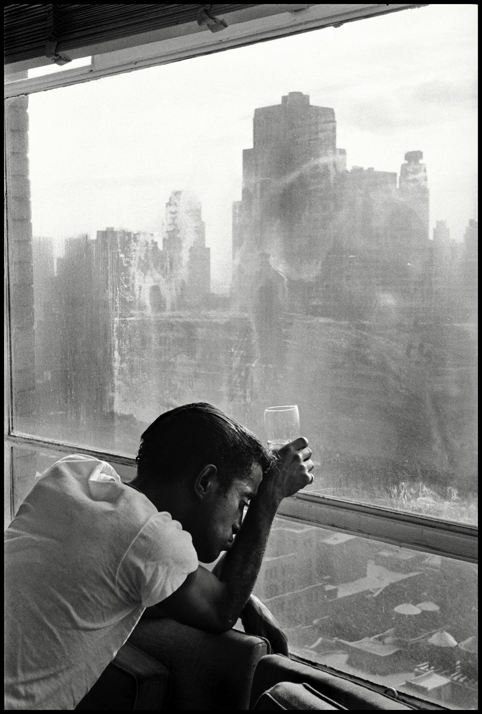 USA. New York City. 1959. Sammy DAVIS Jr. looks out a Manhattan window. Photo by Burt Glinn.