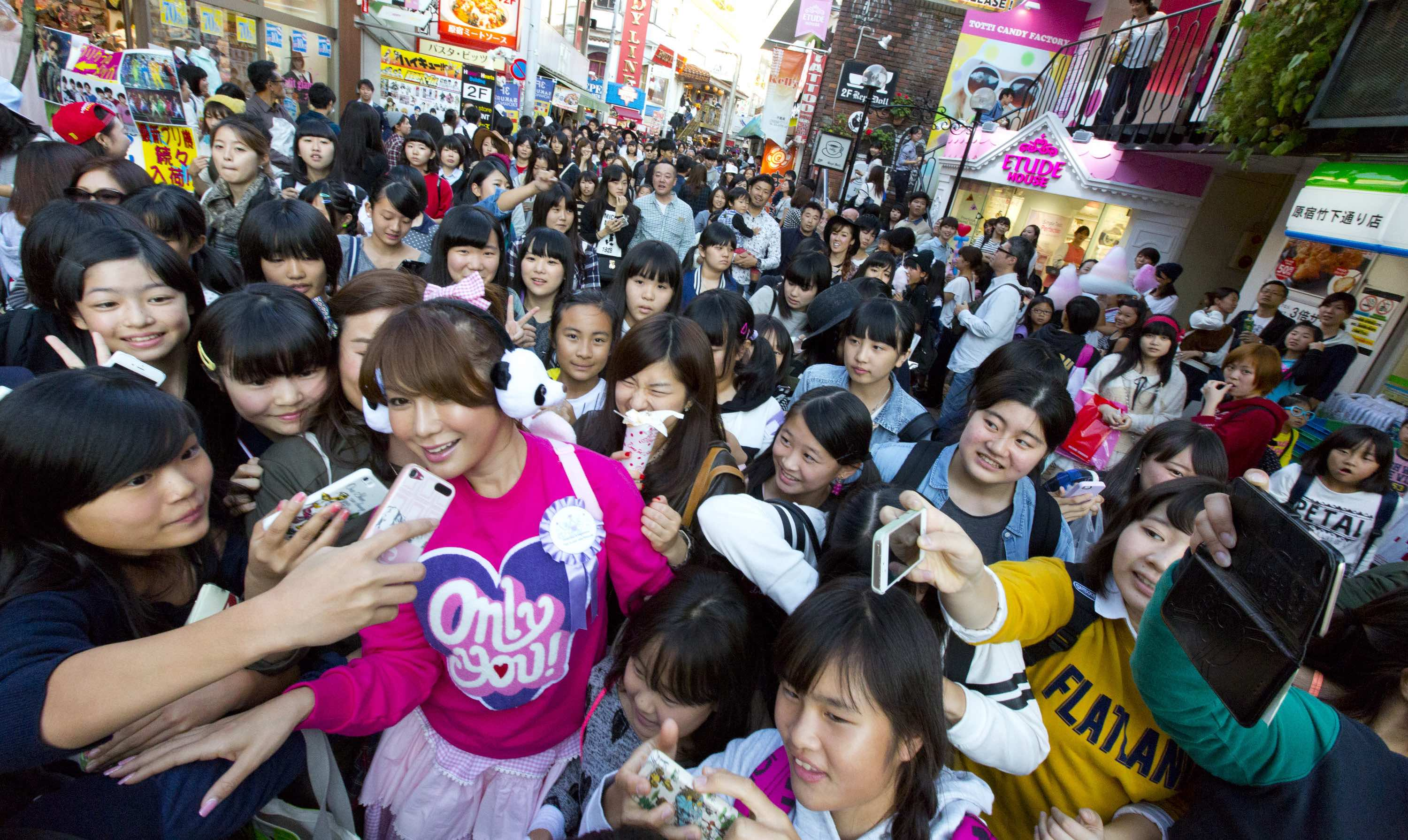 Ai Haruna surrounded by fans in Harajuku, a street popular with teenagers in Tokyo.