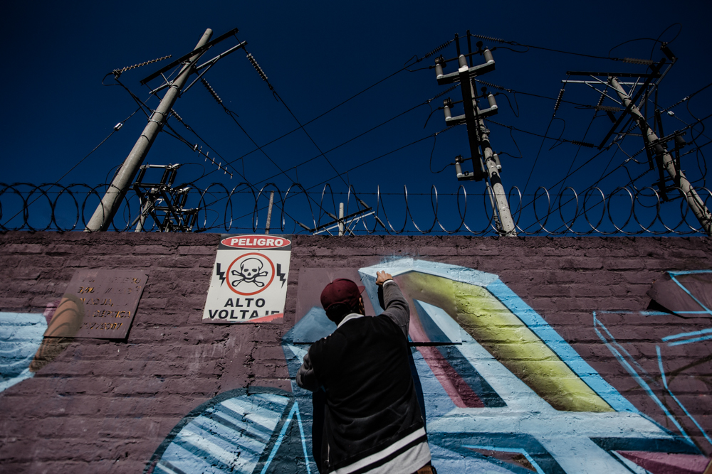 TNT tags the wall of a power station on the main street of Lourdes Colón, La Libertad, in full view of traffic.