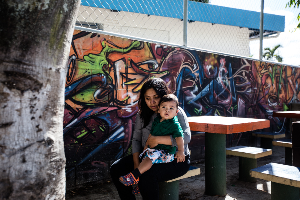 Yerly sits with her son Matías at a local park, next to some graffiti she made for her husband Caesar.