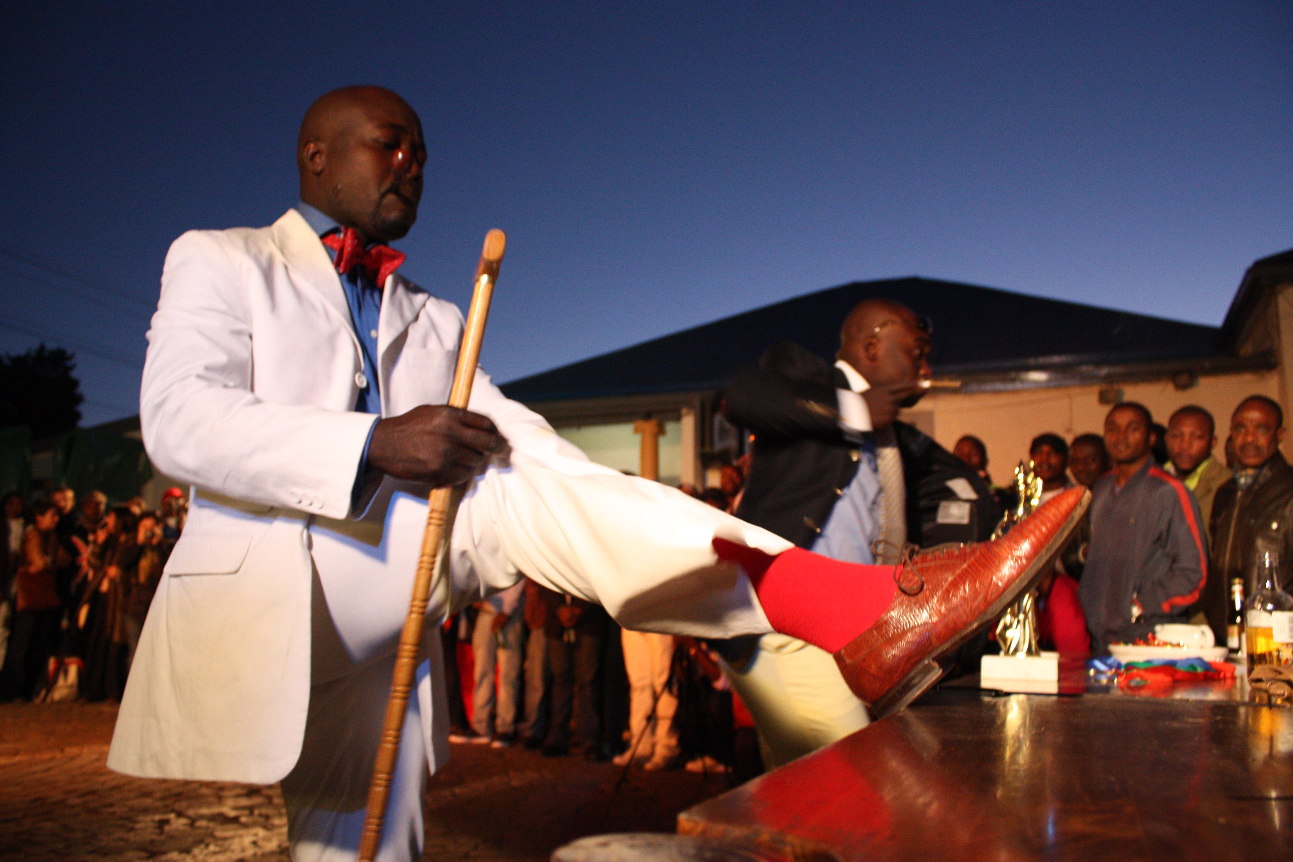 A Congolese national parades in front of fans during the La Sape competition at Kin Malebo restaurant, in Yeoville, Johannesburg South Africa, 30 May 2009. Photography Daniele Tamagni.