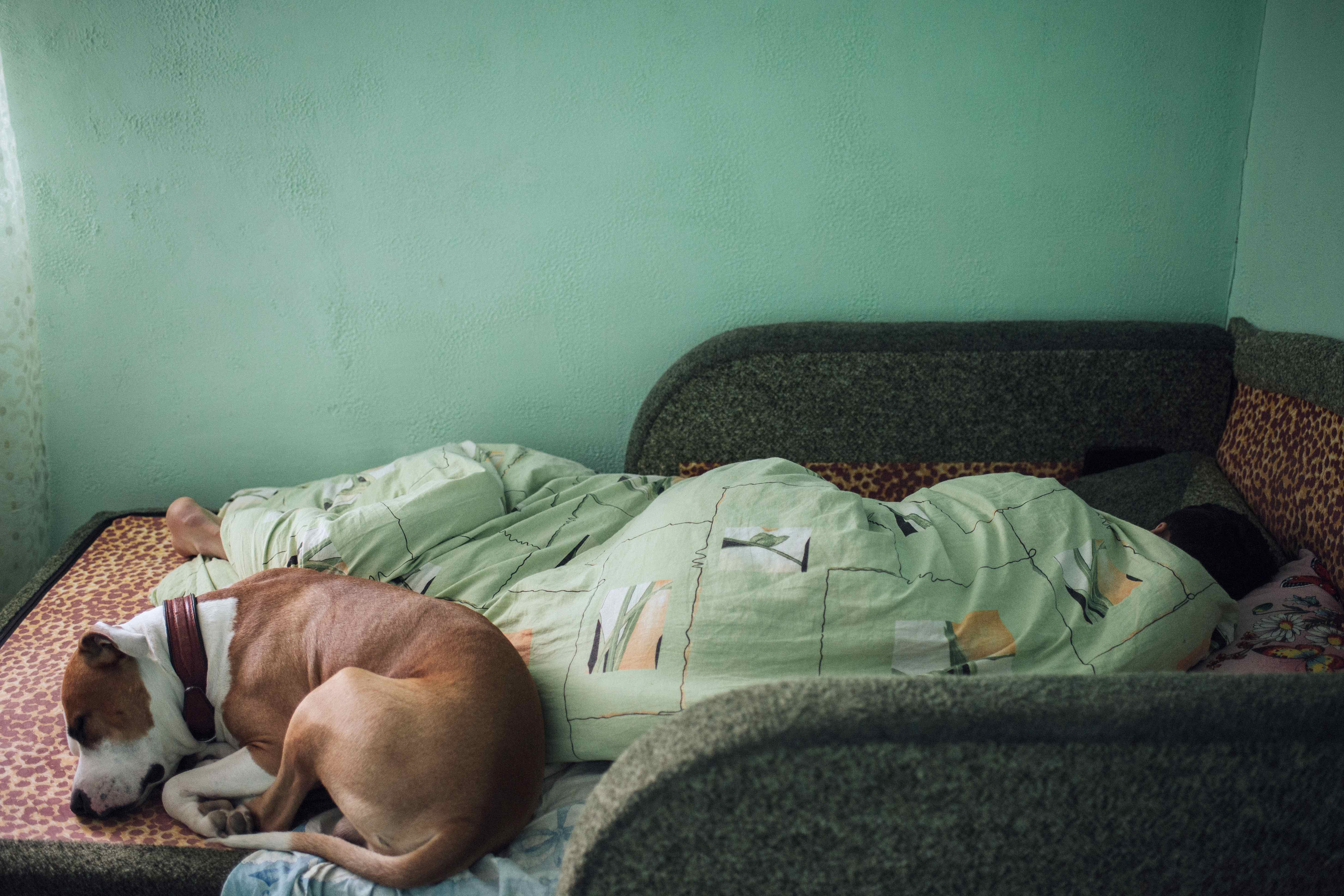 Yura sleeps with his dog Derek at his parents' home in Hristovaia, where he has lived all his life.