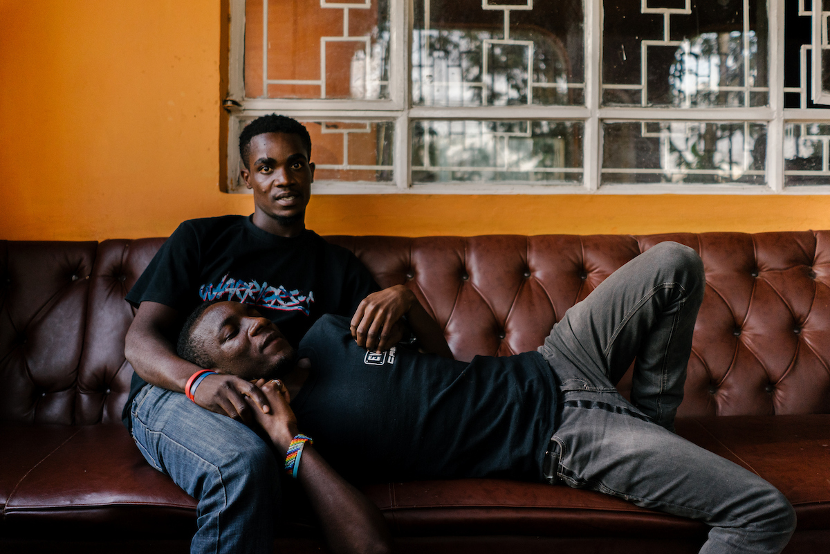 Nelson (lying down) and his boyfriend, who has since been resettled to the US, pose for a portrait at the gated house. Nelson studied theology and sexuality in Uganda and has made it his mission to keep morale in the house high. As such, he writes plays as well as organising games and dances.