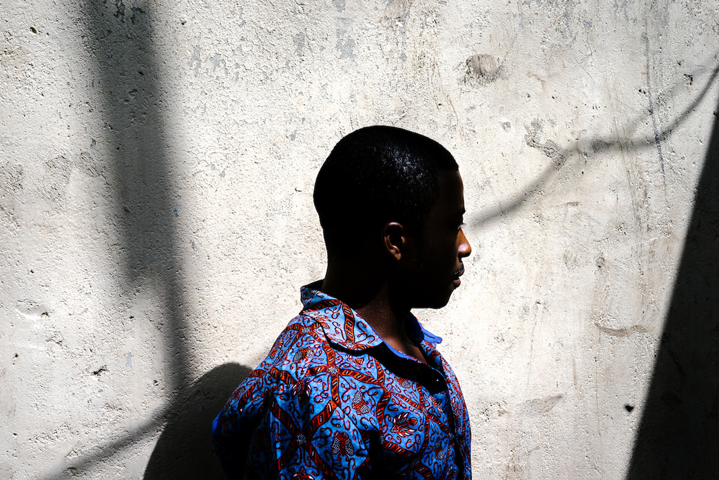 A gay refugee poses for a portrait in front of his home in Nairobi. He was kicked out of his previous apartment by his landlord and beaten by a band of thugs. Now he lives in hiding, sharing a bed with three straight friends who don't know he is gay.