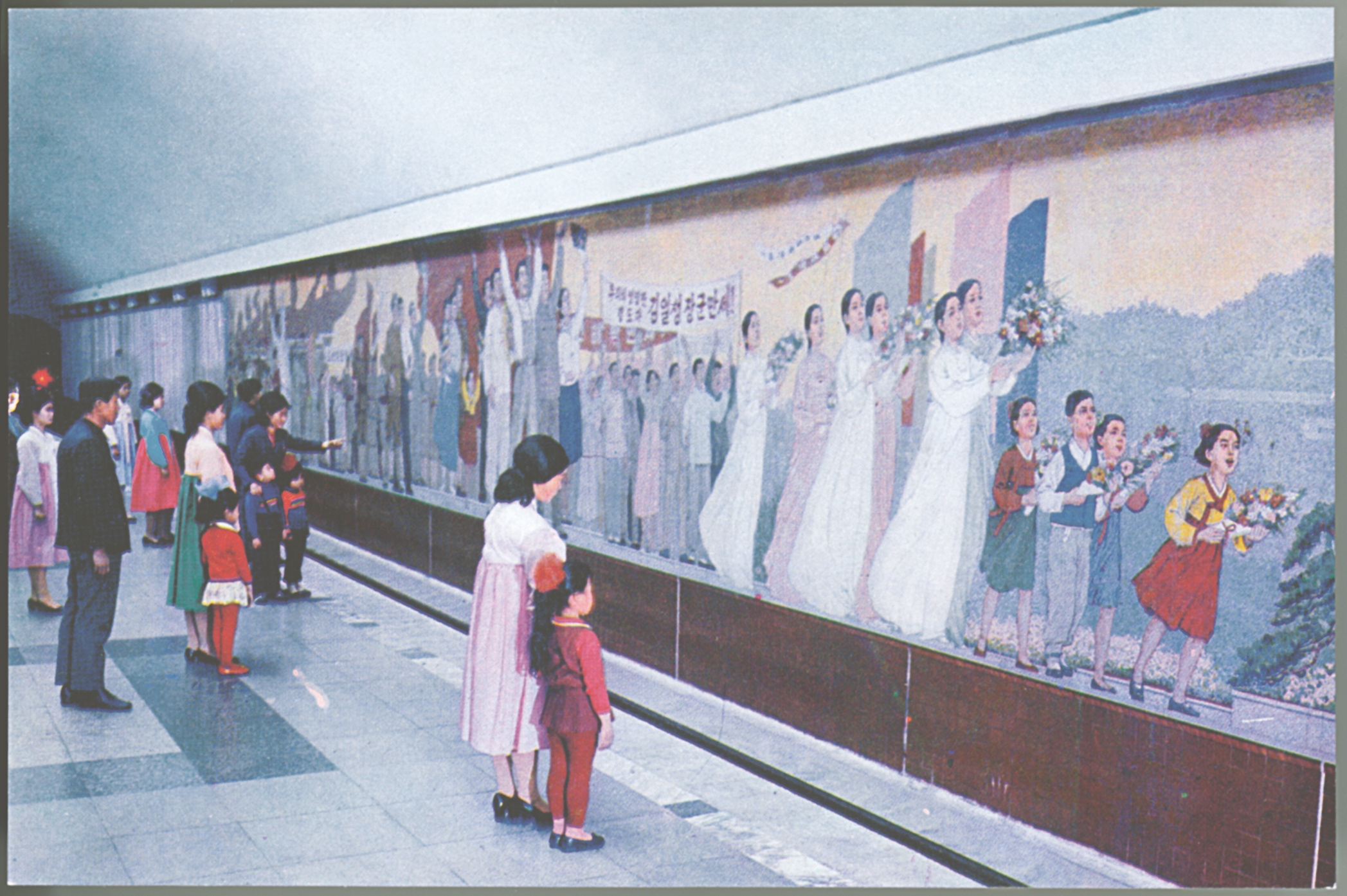 Card from a souvenir set of Pyongyang Metro postcards. In the 1990s and early 2000s there were rumours in the Western press that graffiti was being etched on to the windows of the Pyongyang Metro carriages. In fact, the carriages had been imported second-hand from West Berlin and the graffiti (impossible to remove from glass) was therefore in German.