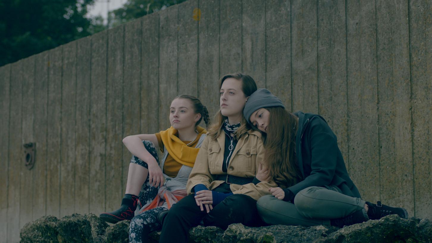 3 The girls sit watching