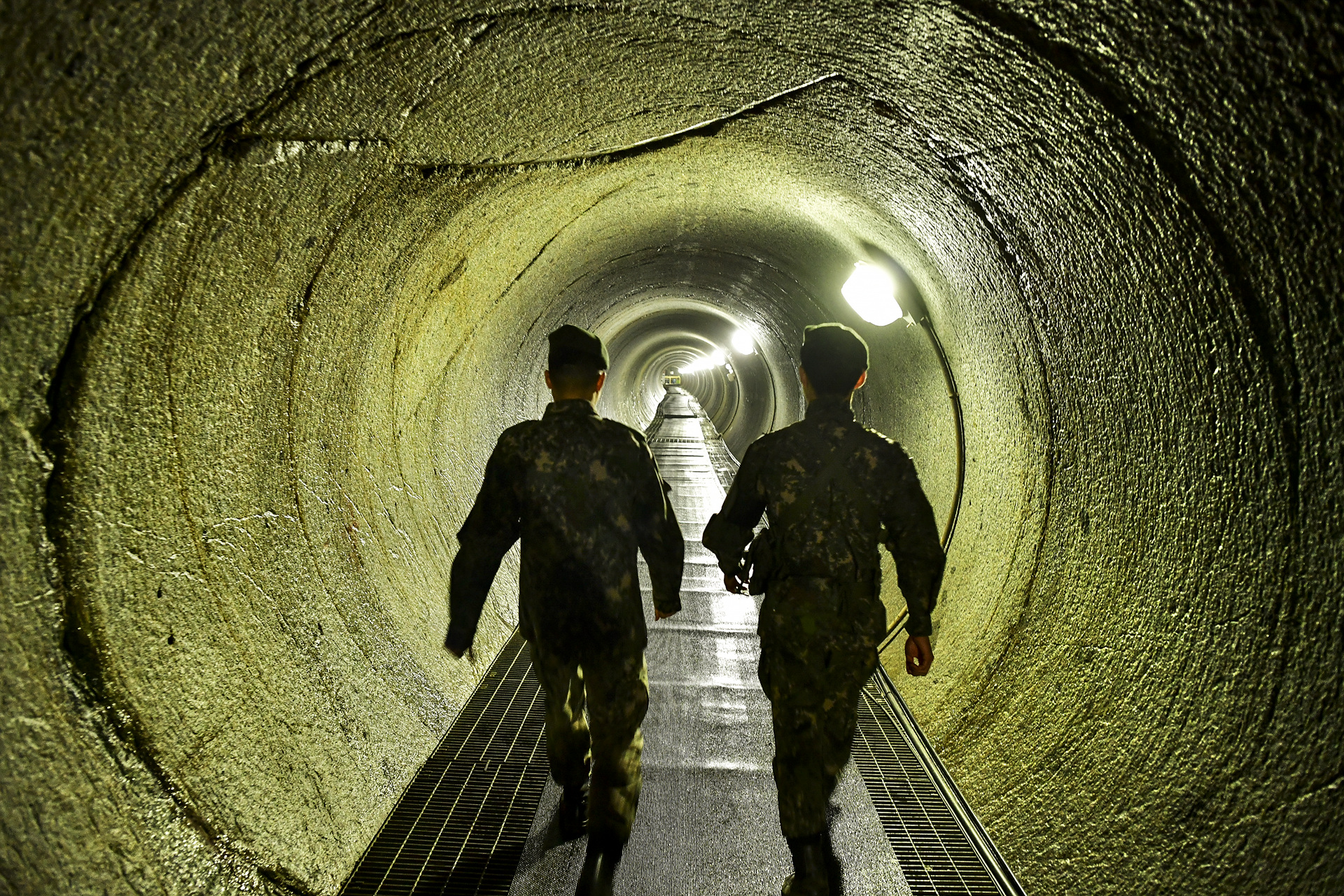 Two South Korean soldiers walk along the long counter tunnel connecting to the North Korean infiltration tunnel.