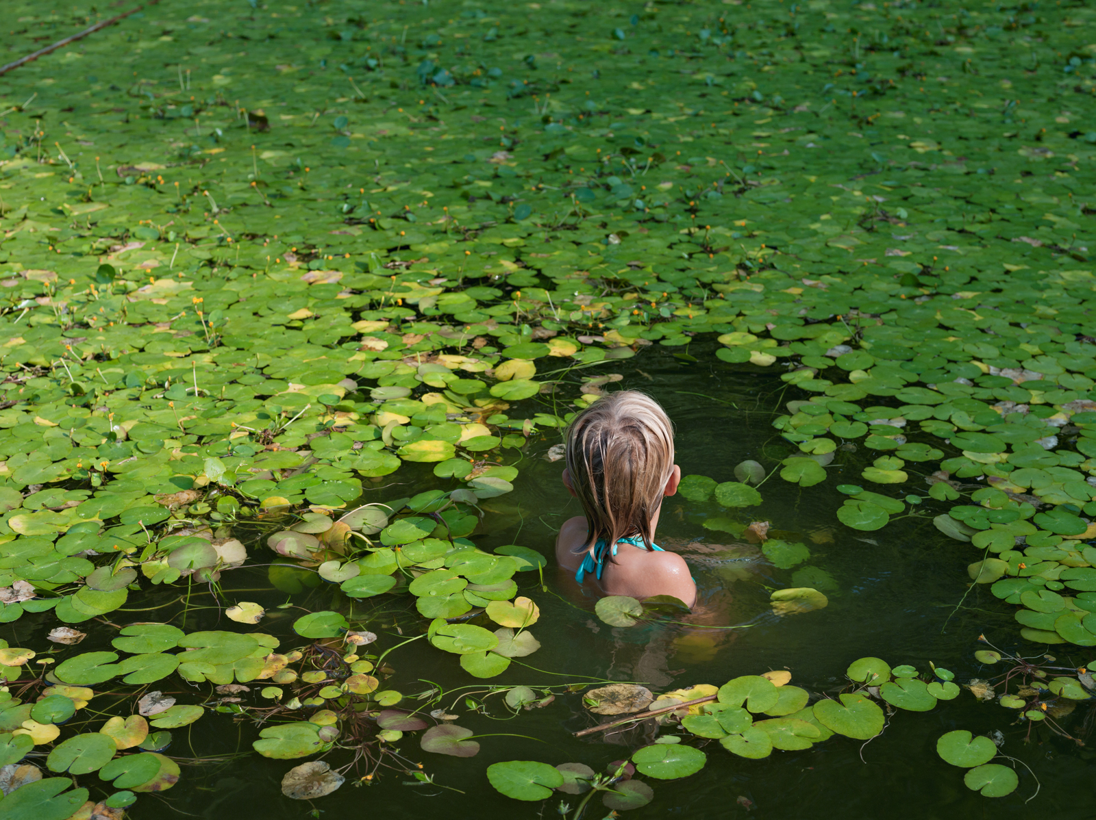 Maddie with invasive water lilies, North Carolina. © Lucas Foglia, courtesy of Michael Hoppen Gallery, London.
