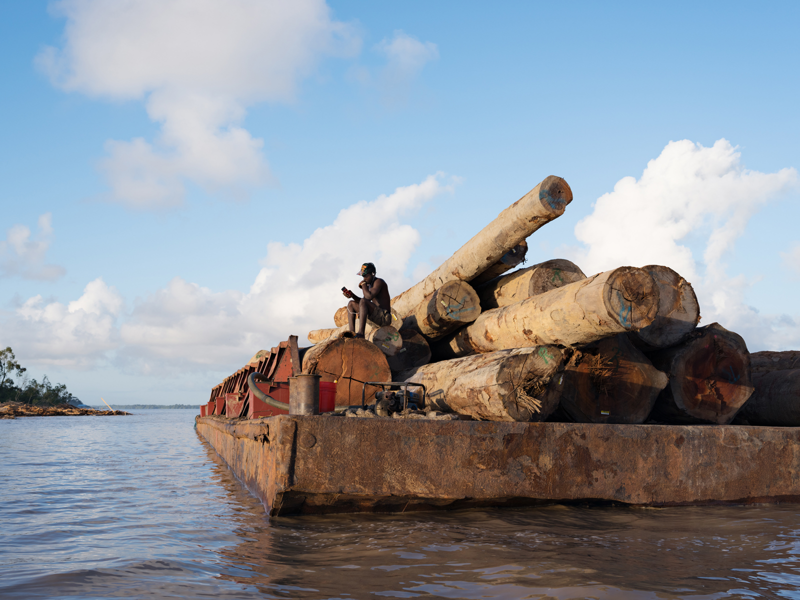 Kurt guarding logs for export to China, Essequibo River, Guyana. © Lucas Foglia, courtesy of Michael Hoppen Gallery, London.