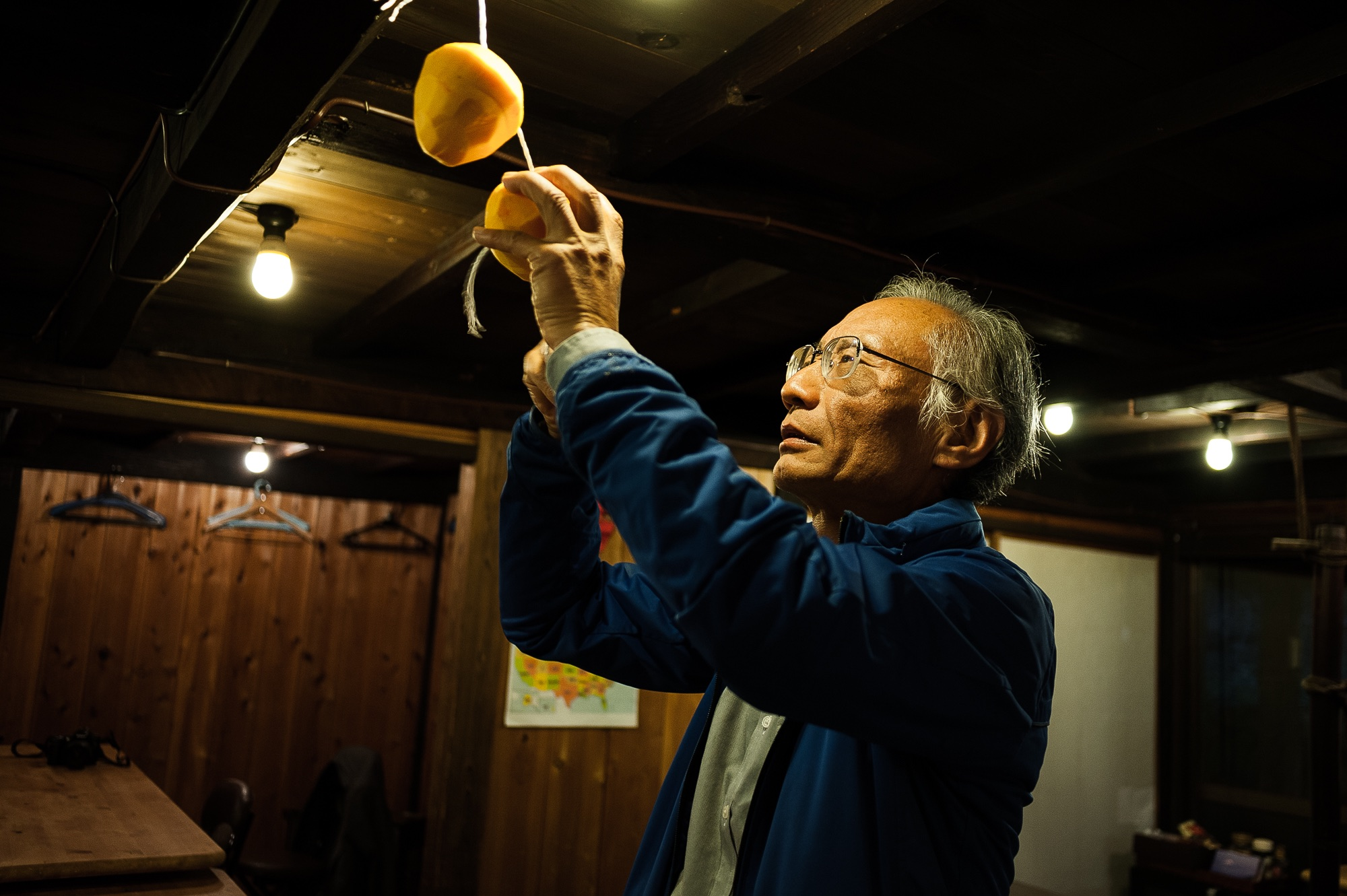 Within the community building, a local man hangs persimmons to dry on string