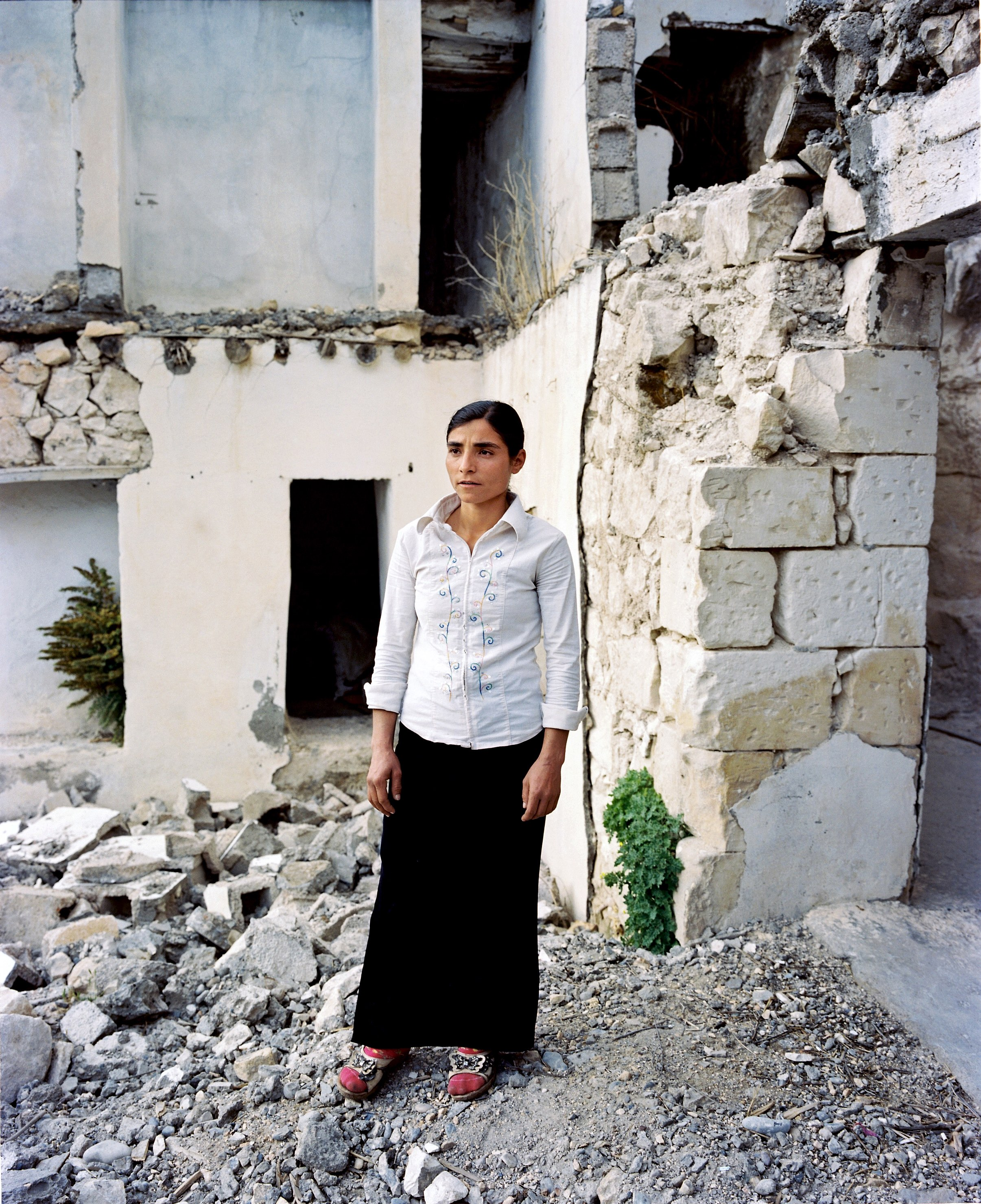 A woman stands in the ruins of the flooded village of Savaçan, facing the reservoir lake of the Birecik Dam on the Euphrates River.
