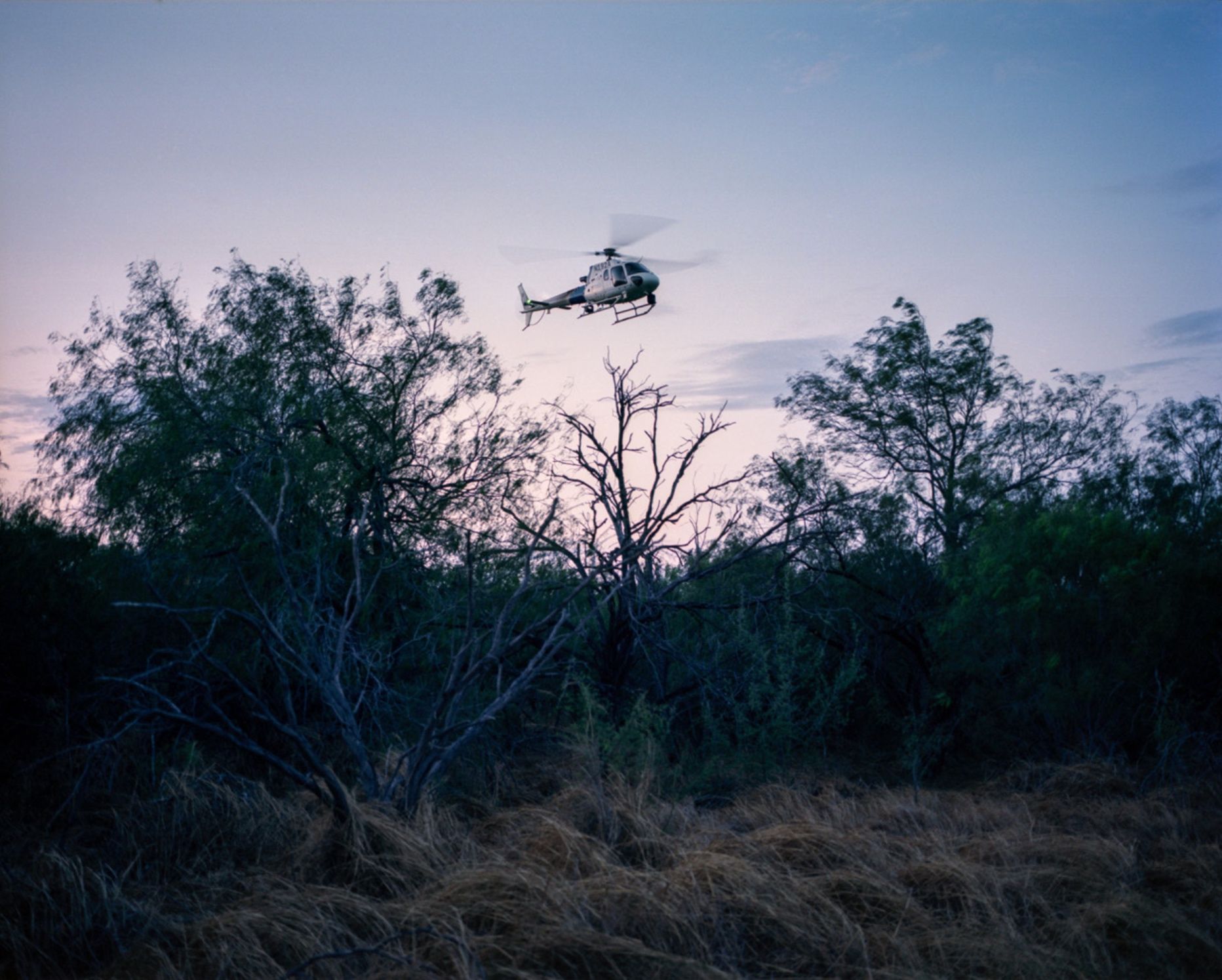 A US Border Patrol helicopter searches the brush for two men who were spotted by agents. They were never found.