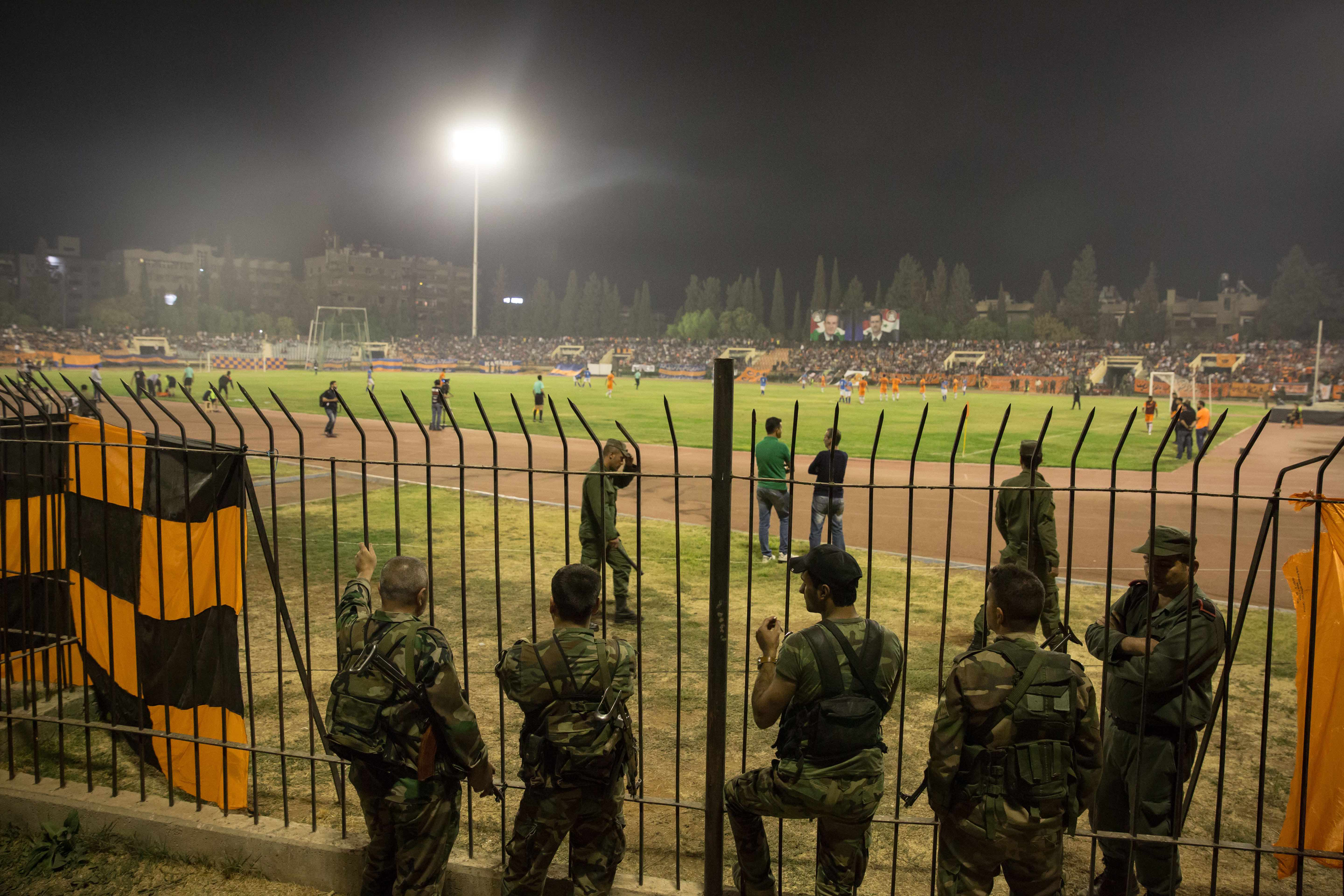 Soldiers line the pitch during the Syrian Cup final. Some also stood in the crowd, watching out for security breaches.