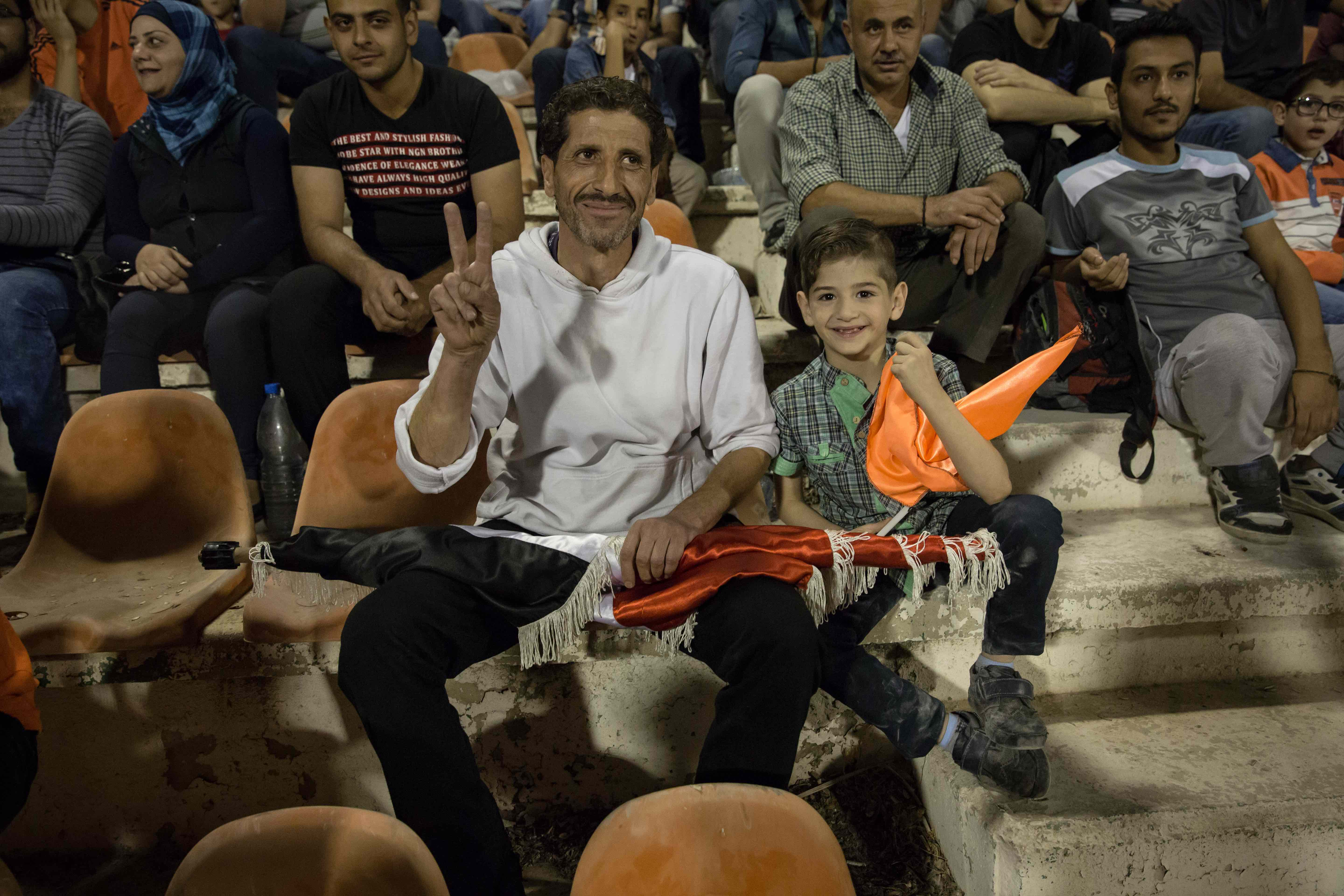 A father and son watch the match from the stands. Many parents said they are still too afraid to bring their children to games.