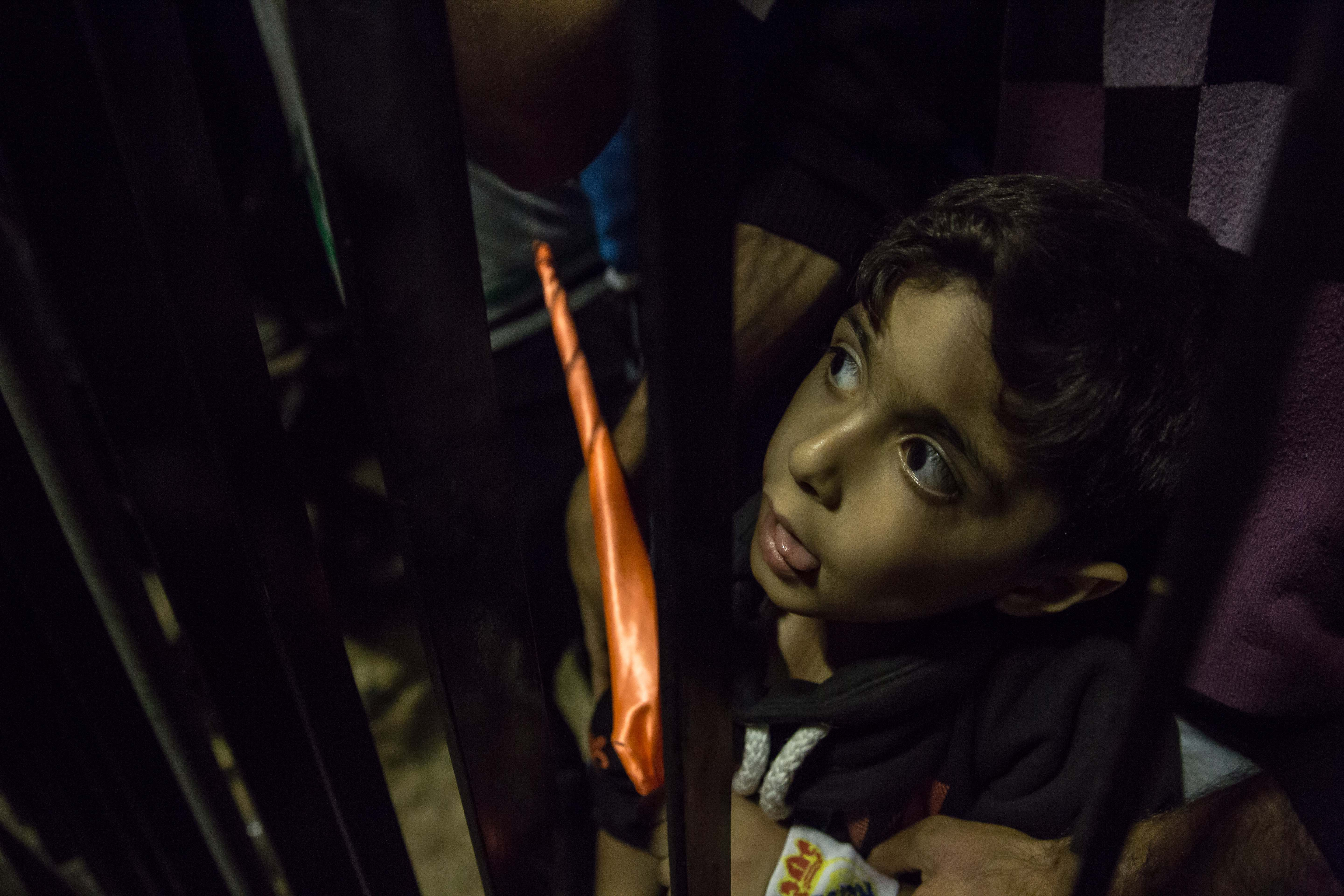 A boy gazes through bars at the game in Tishreen Stadium.