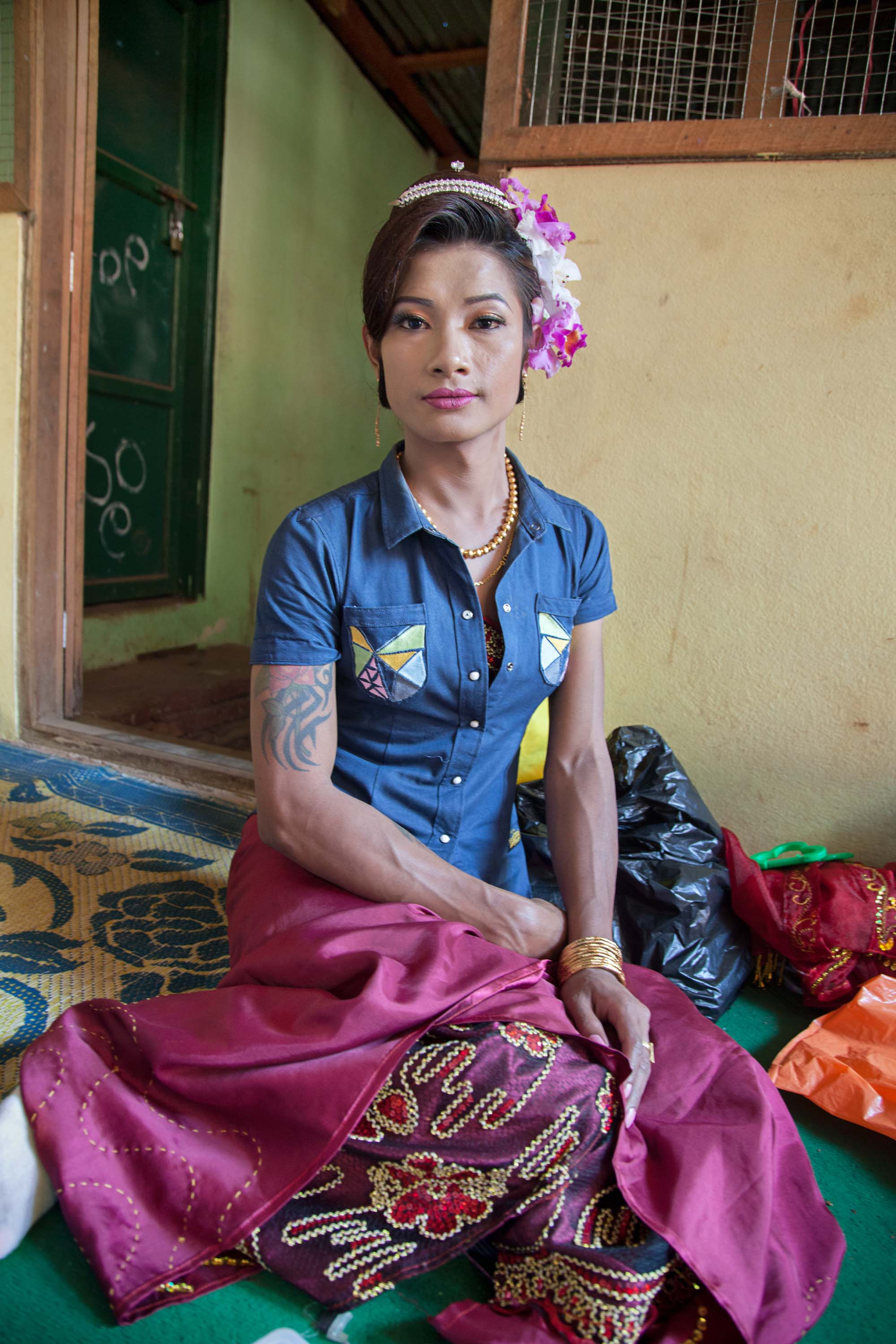 A gender variant tattooed and muscular nat kadaw in Mount Popa waits to perform at a nat pwe.
