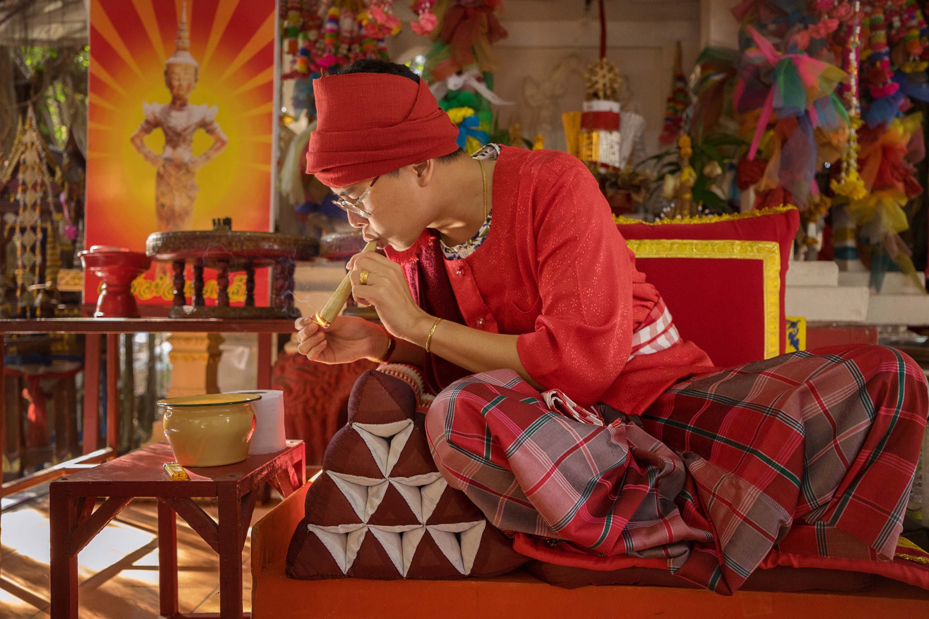 A maa khii in Chiang Mai lights a traditional cigar for the enjoyment of their spirit.