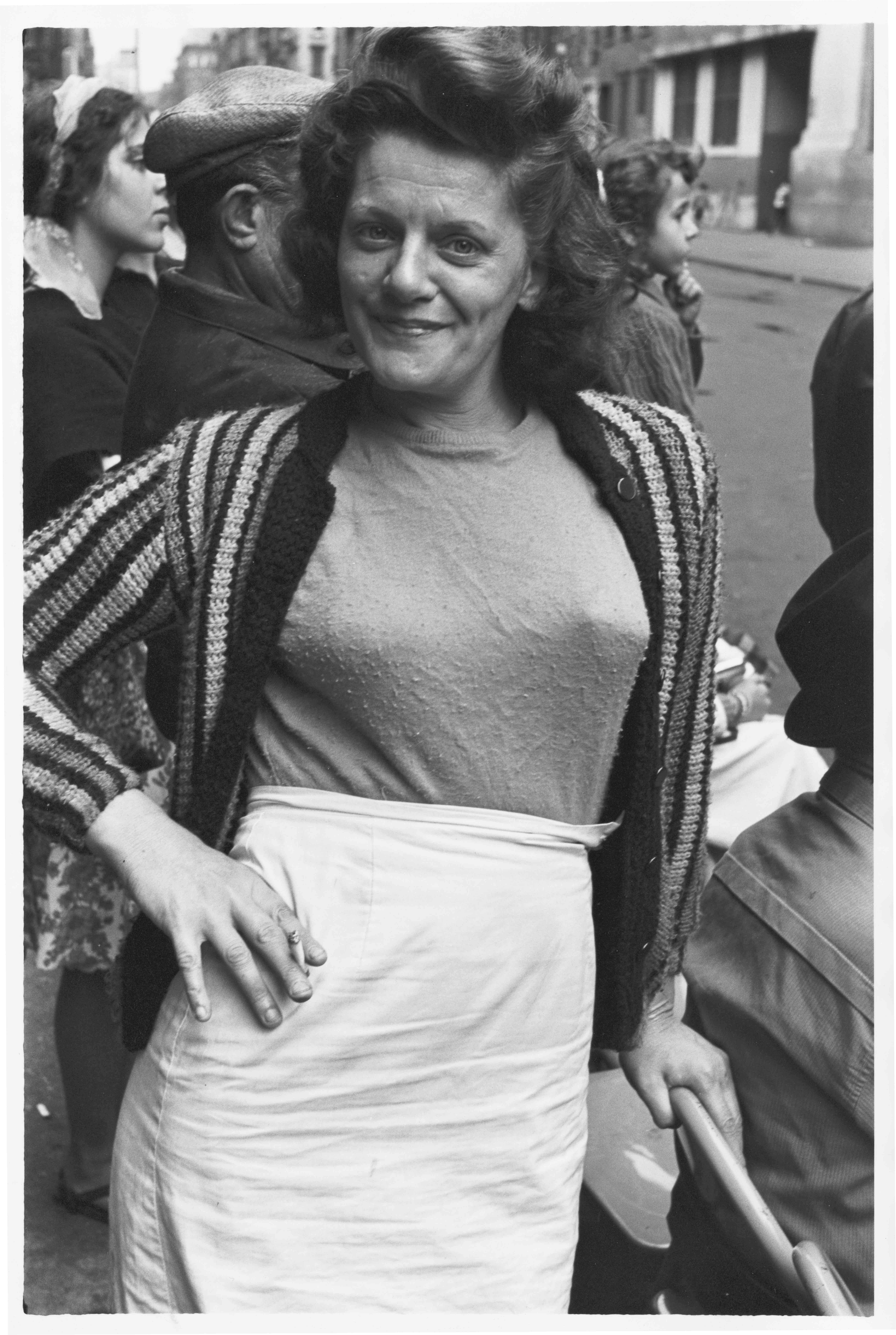 Woman with her hand on her hip, holding a cigarette, 1963