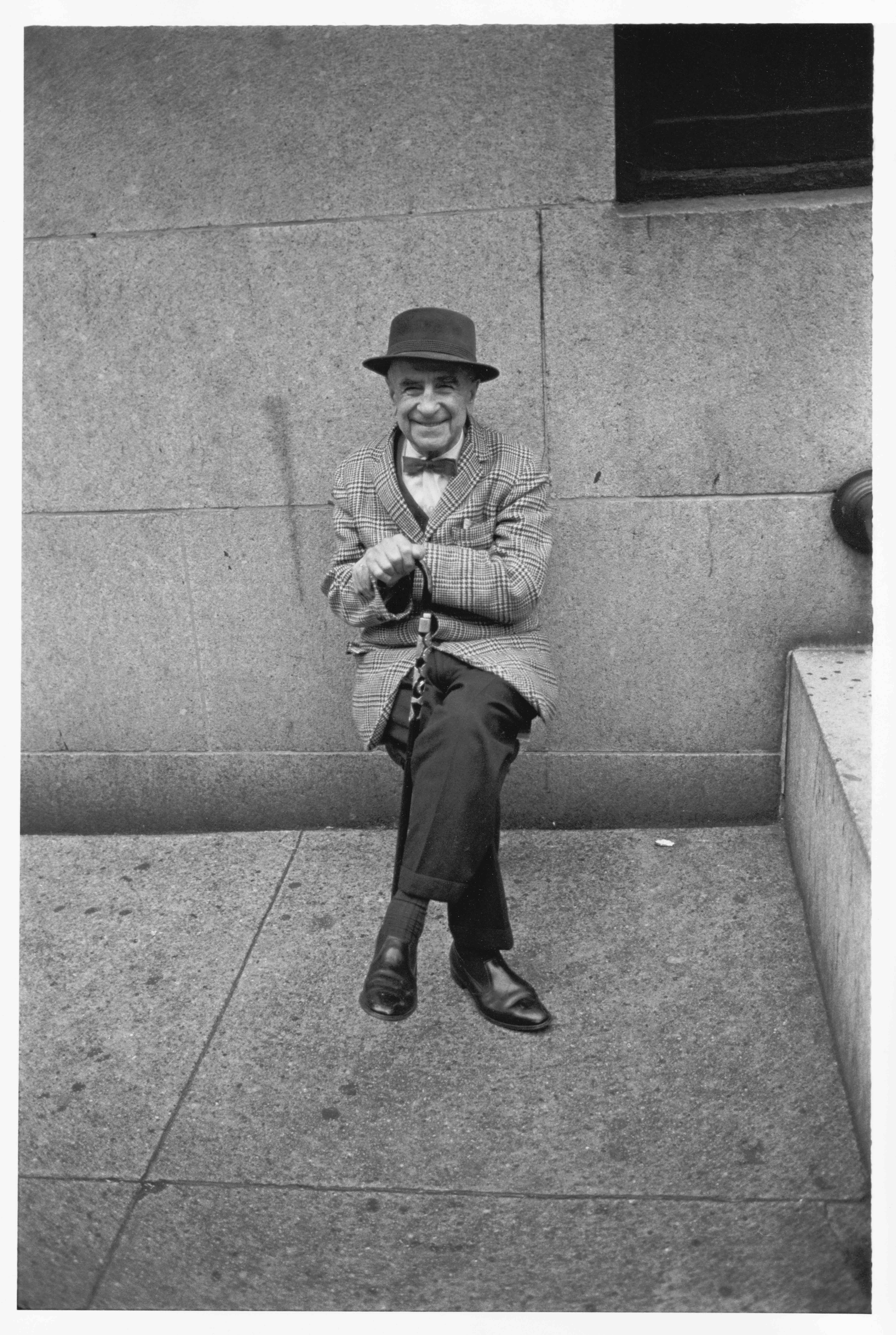 Gentleman resting at the side of a building, 1967