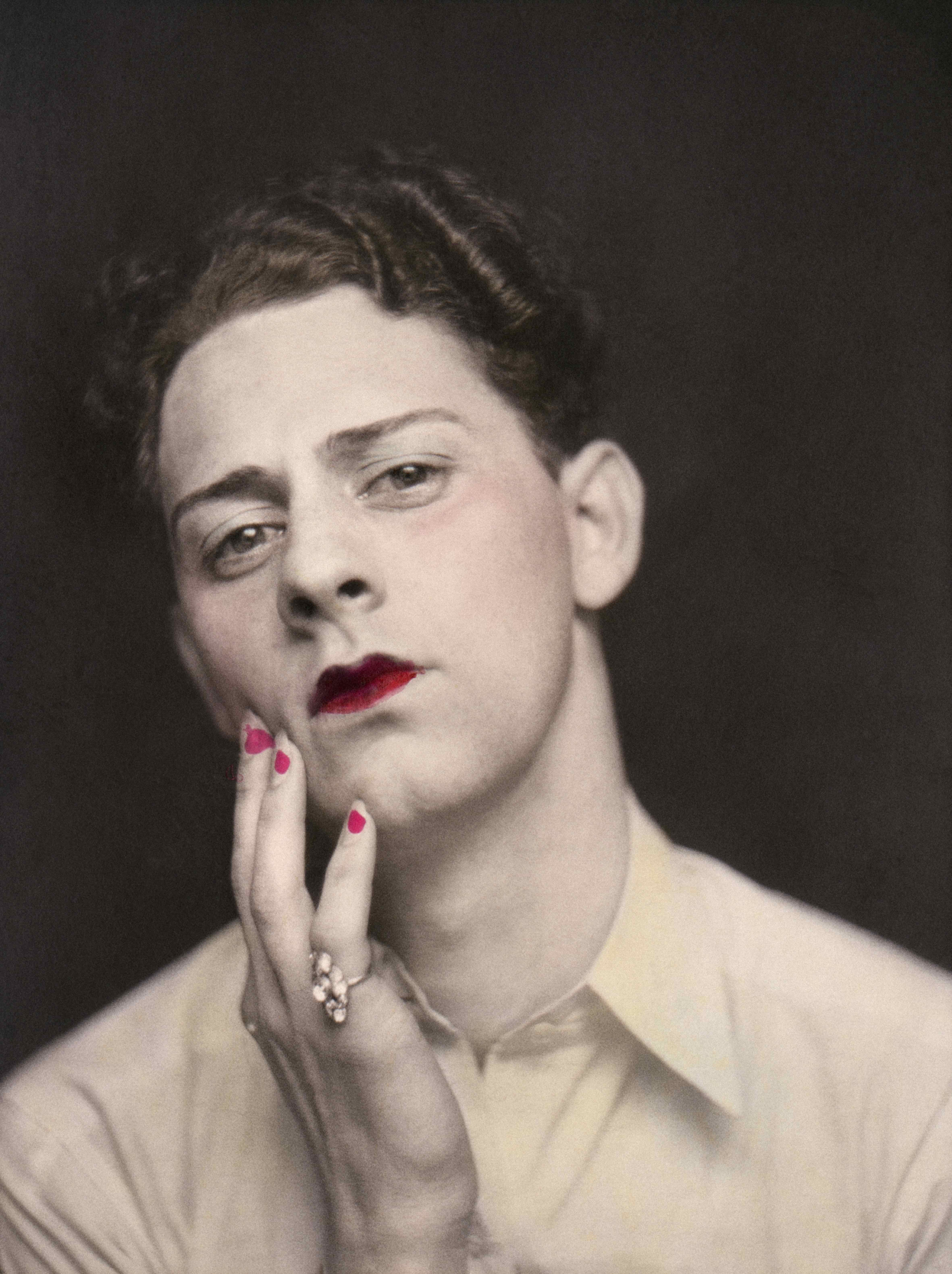 Man in makeup wearing ring. Photograph from a photo booth, with highlights of colour. United States, circa 1920.